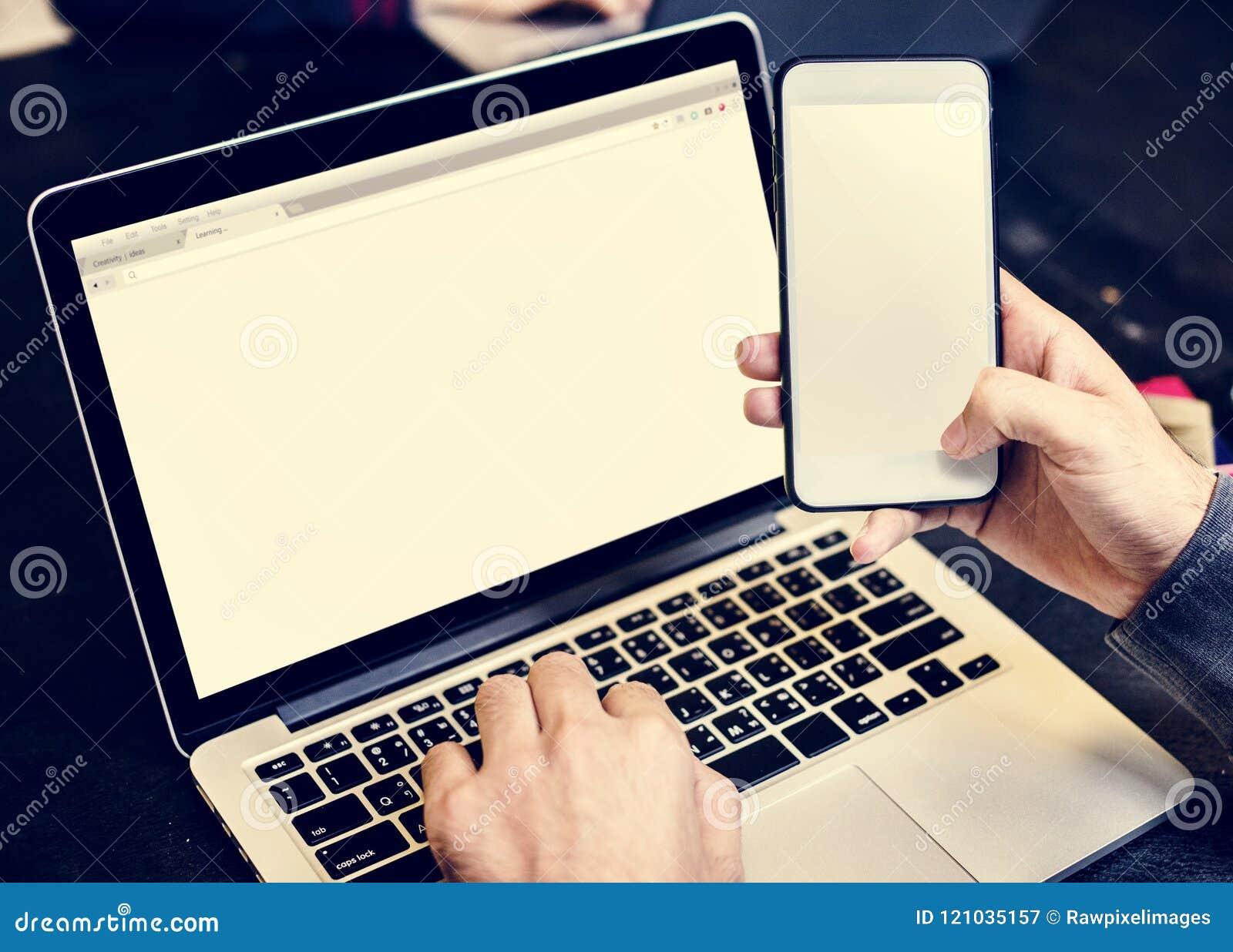 Nahaufnahme von den Händen, die Handy mit Computerlaptophintergrund halten