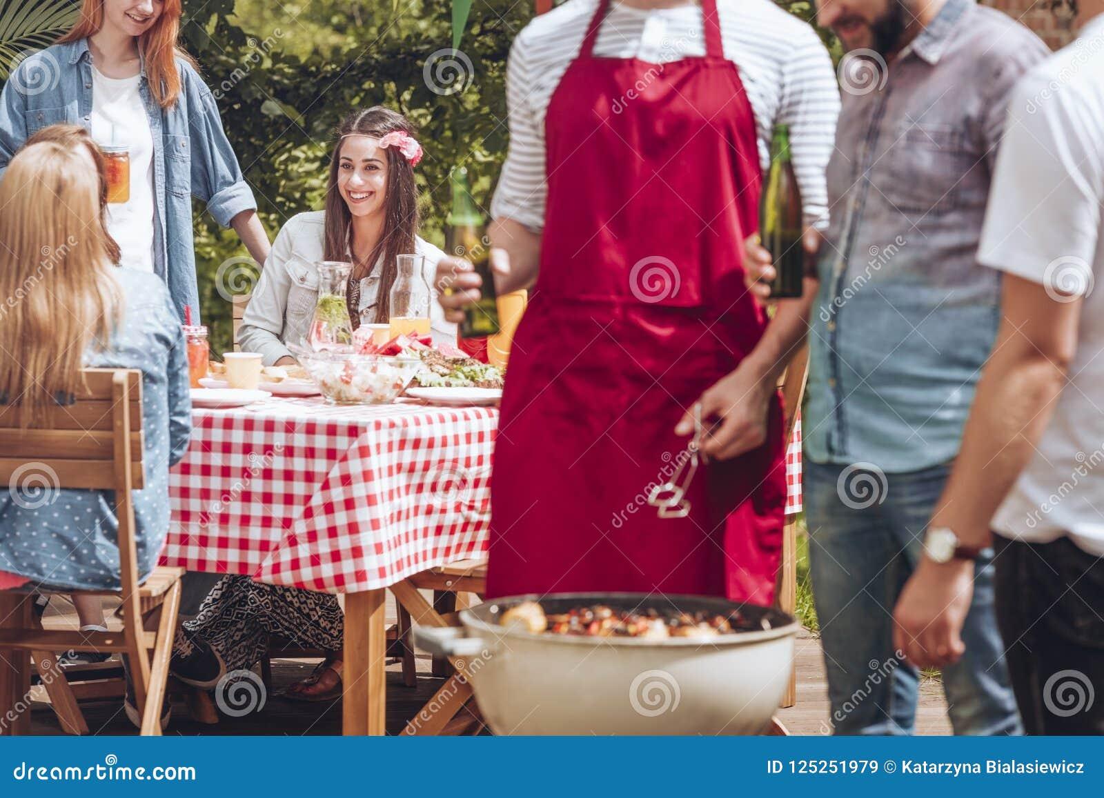 Nahaufnahme von den Männern, die über einem Grill mit shashliks stehen und sprechen