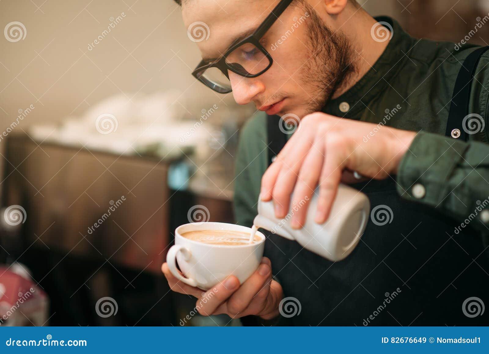 Nahaufnahme von den männlichen Händen, die Creme Kaffee hinzufügen