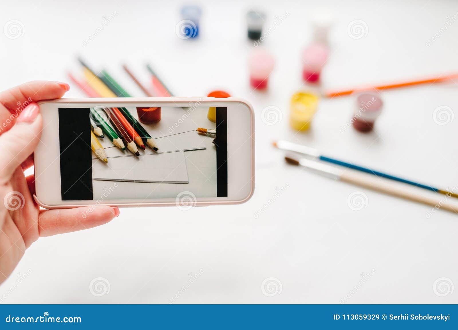 Nahaufnahme von Frau ` s übergibt die Herstellung des Fotos am Handy: Arbeitsplatz des Künstlers für das Zeichnen: farbige Bleist