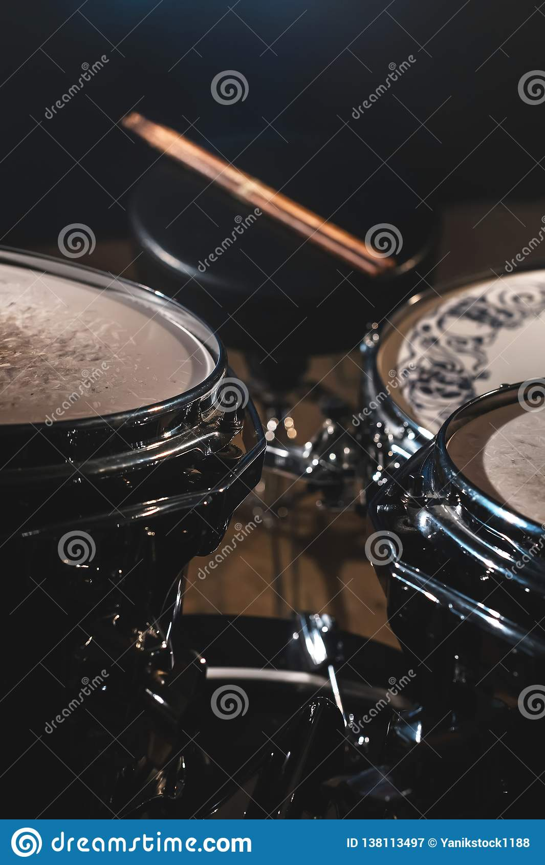 Nahaufnahmeansicht eines der Trommel Satzes und Trommelstöcke in einem dunklen Studio Schwarze Trommelkörper mit Chromordnung Das