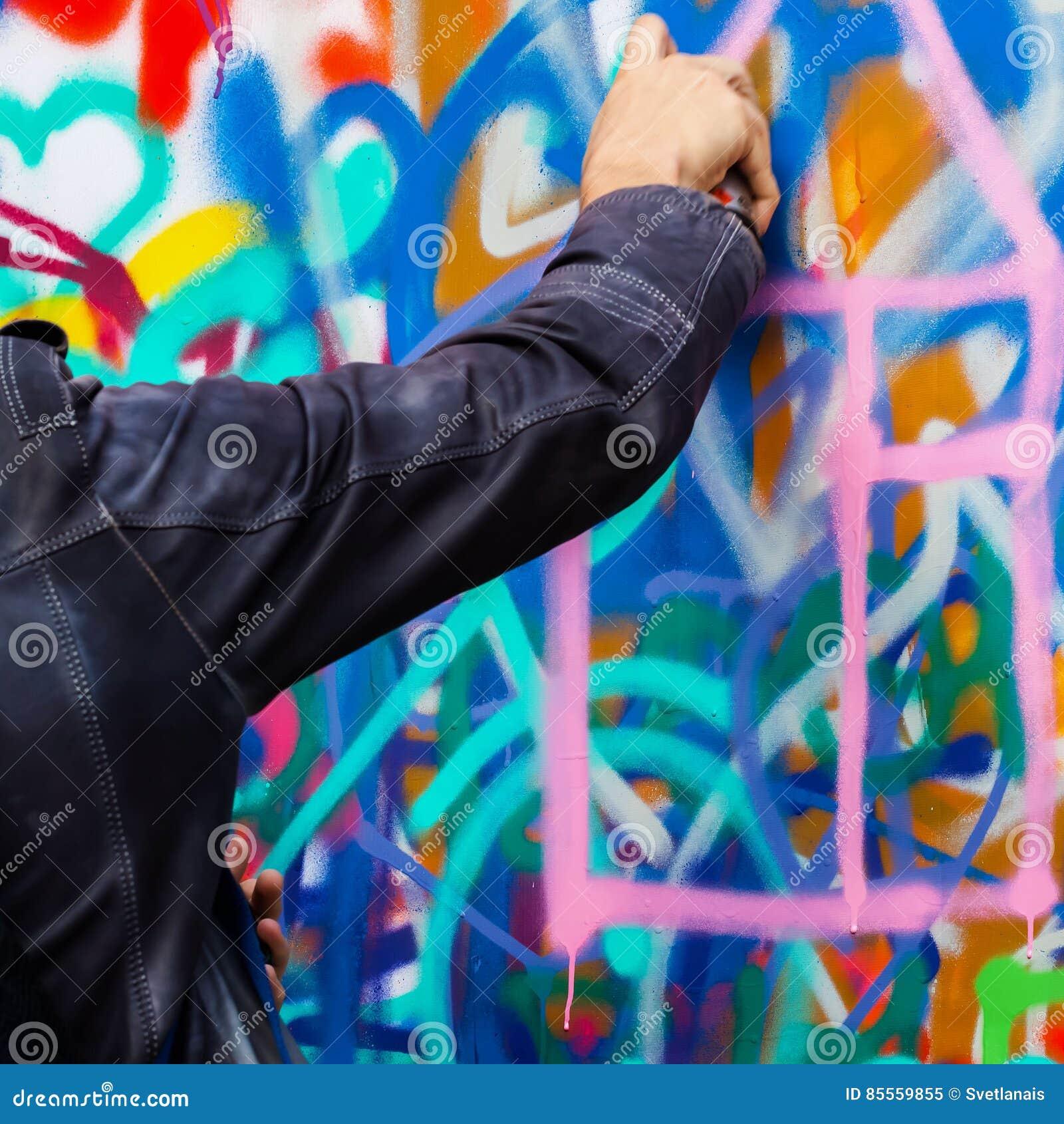 Nahaufnahmearm des jungen Kerls bunte Graffiti auf der Wand, modernes Design des Konzeptes zeichnend