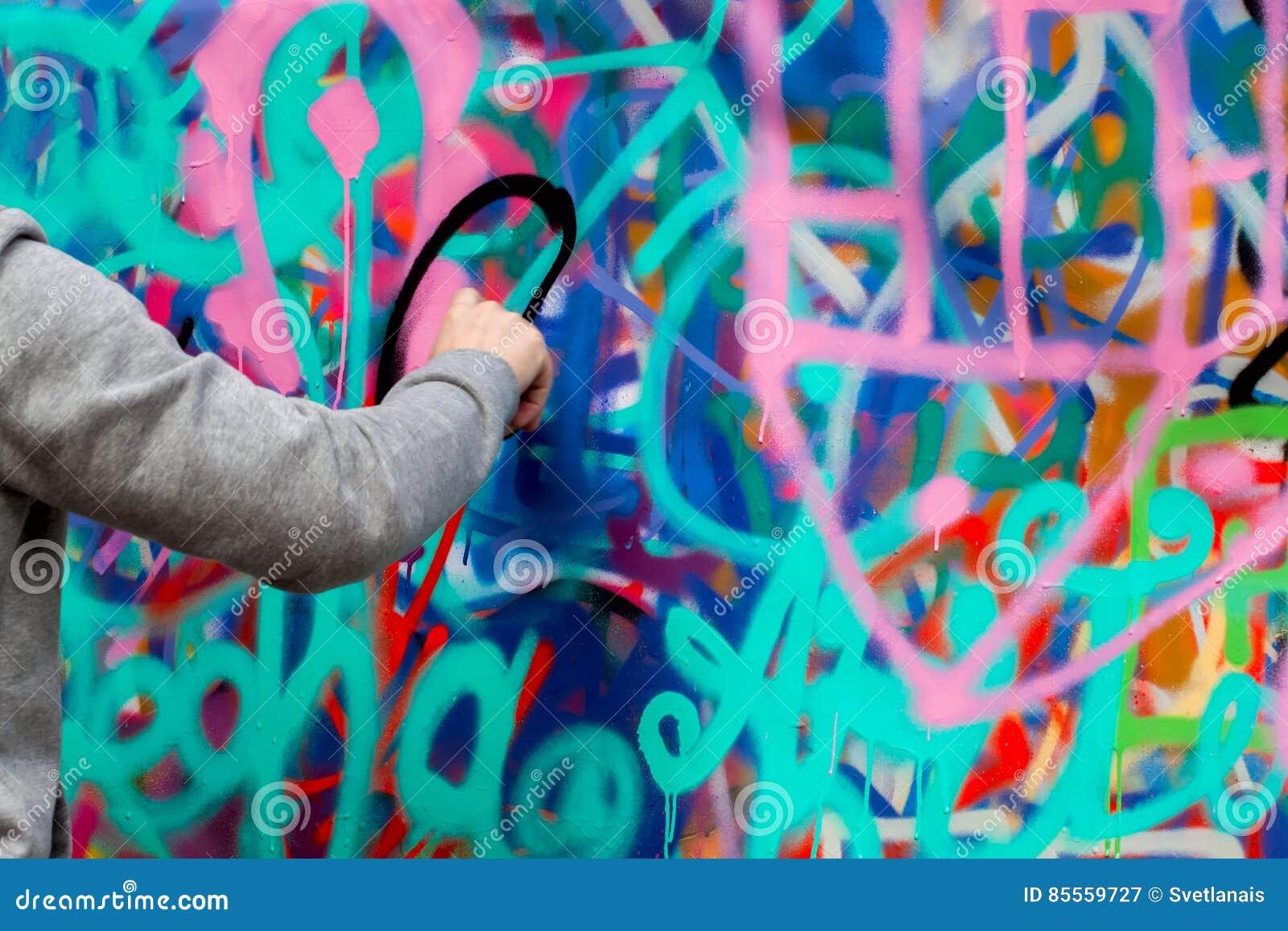 Nahaufnahmearm des jungen Kerls bunte Graffiti auf der Wand zeichnend Konzeptzeitgenossekultur
