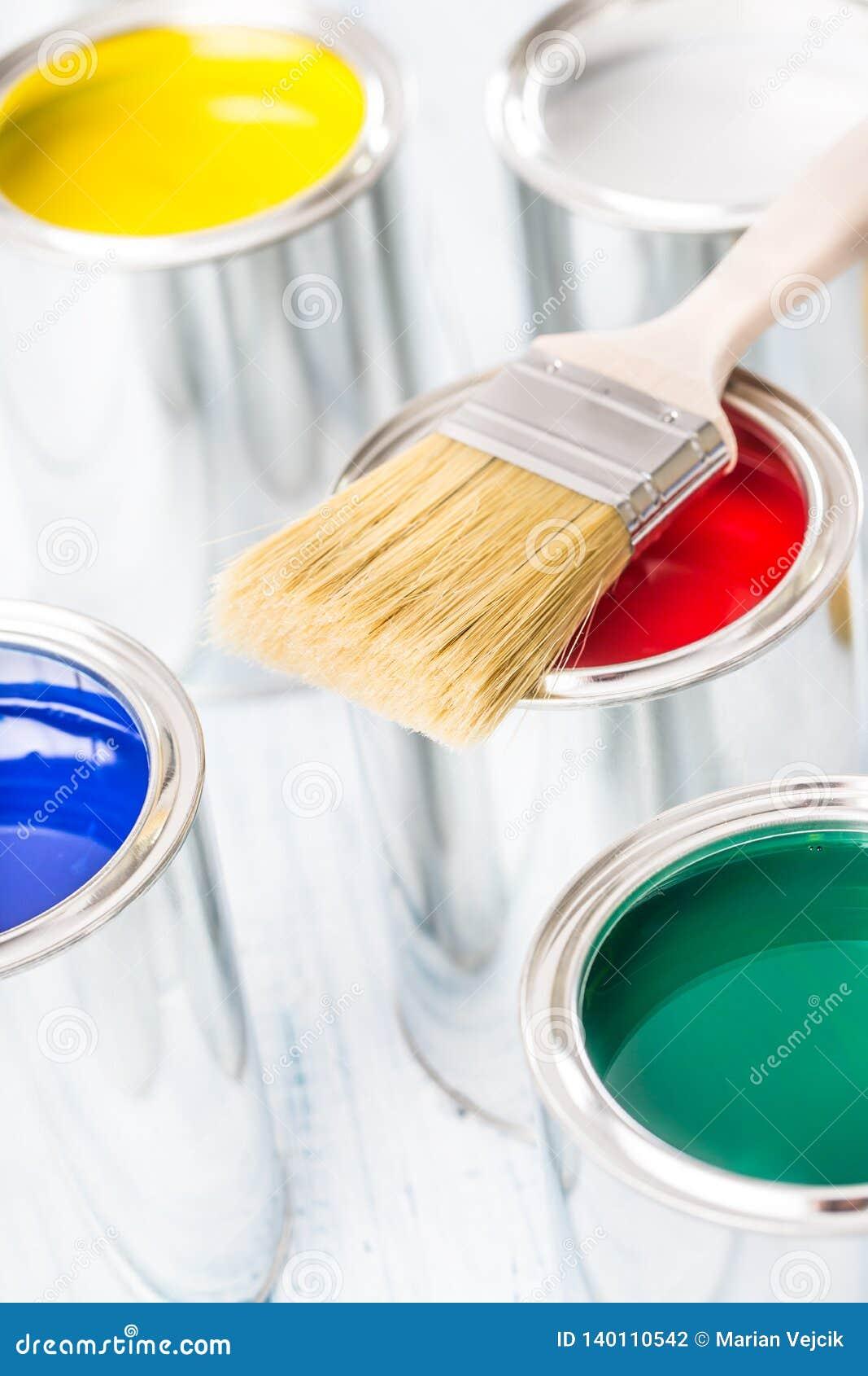 Nahaufnahmebürsten, die auf mehrfarbigen Farbendosen liegen