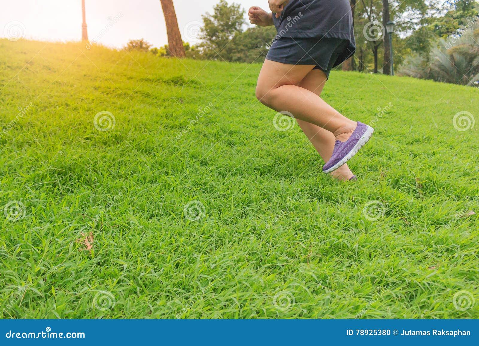 Nahaufnahmebeine rütteln im Park auf dem grünen Gras,