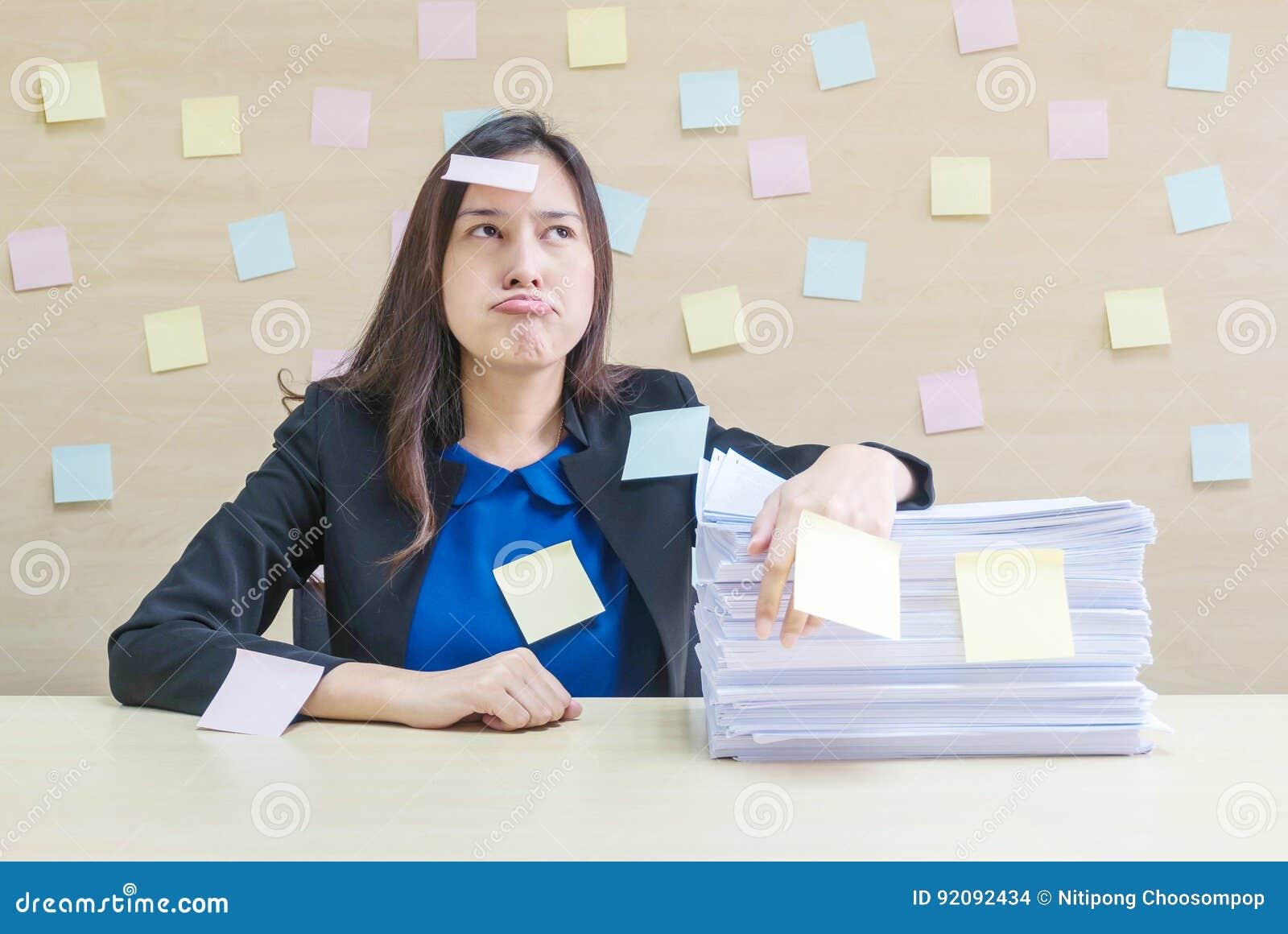 Nahaufnahmeberufstätige frau bohren vom Stapel der harten Arbeit und des Arbeitspapiers vor ihr im Arbeitskonzept auf unscharfem