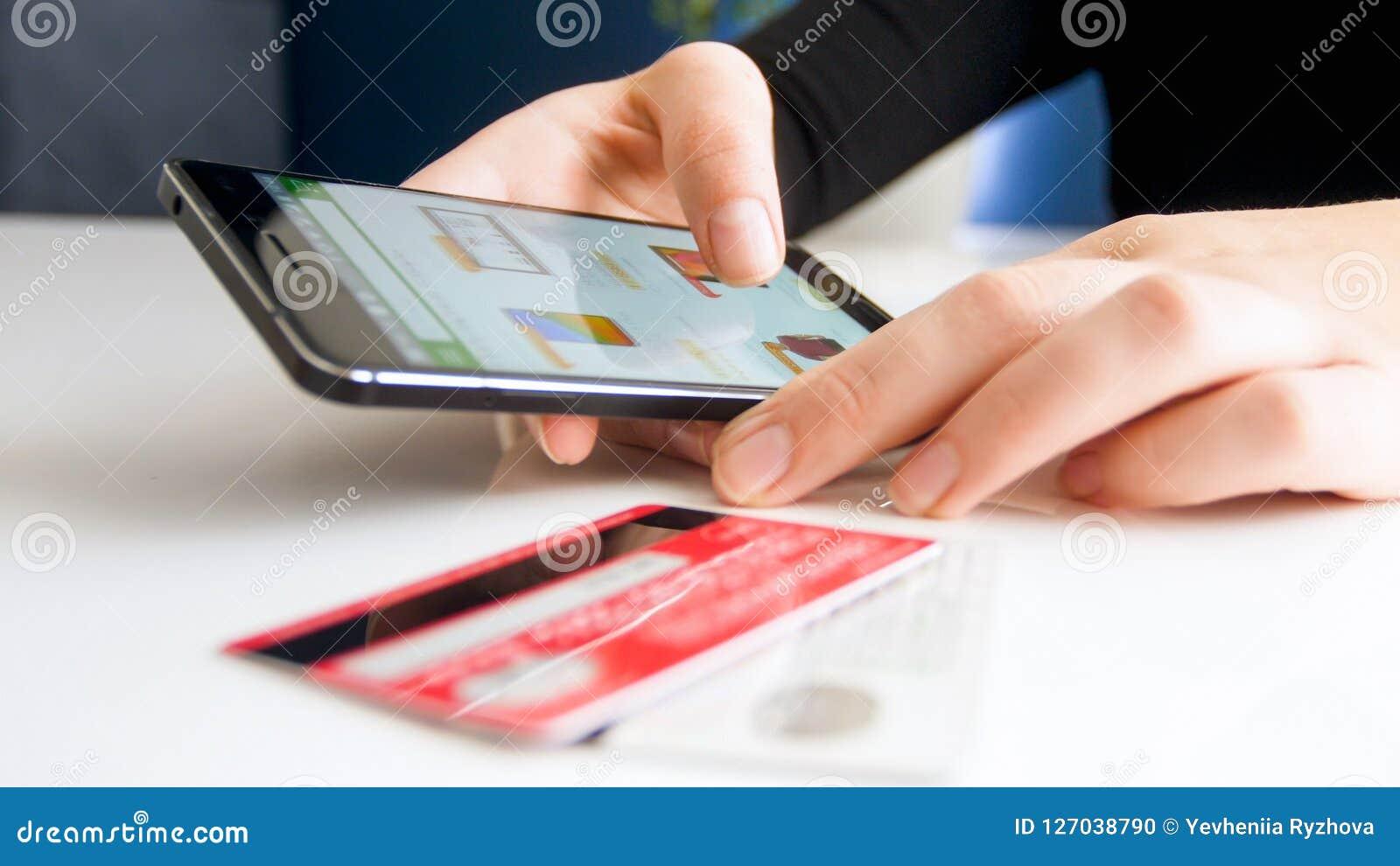 Nahaufnahmebild der jungen Frau on-line-Bestellung auf Smartphone machend und mit Kreditkarte zahlend