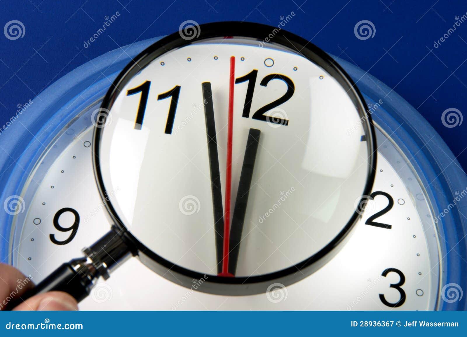 Nahaufnahmeborduhrhände ungefähr, zum des Mitternacht oder des Mittages durch Vergrößerungsglas zu schlagen