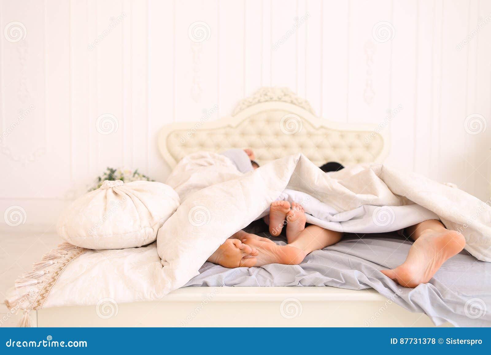 Nahaufnahmefamilienfusse Die Auf Bett Liegen Und Schlafen Stockfoto
