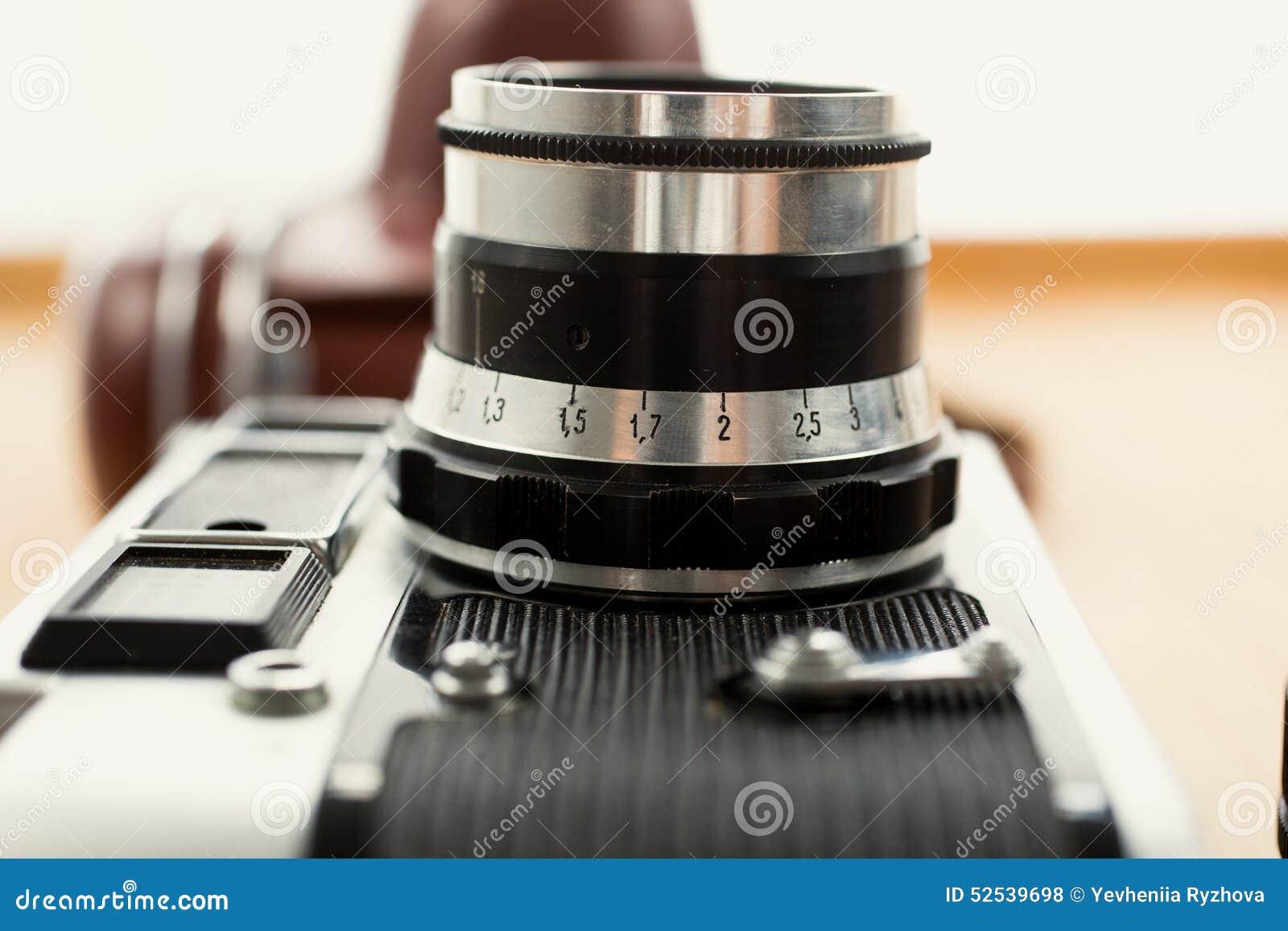 Nahaufnahmefoto der Weinlesekamera liegend auf hölzernem Schreibtisch