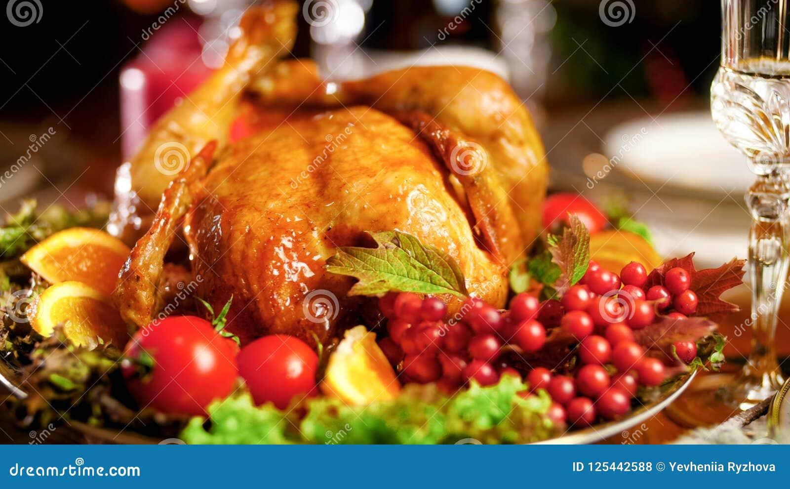 Nahaufnahmefoto des gebratenen Huhns auf großem Teller auf Weihnachtsessentabelle