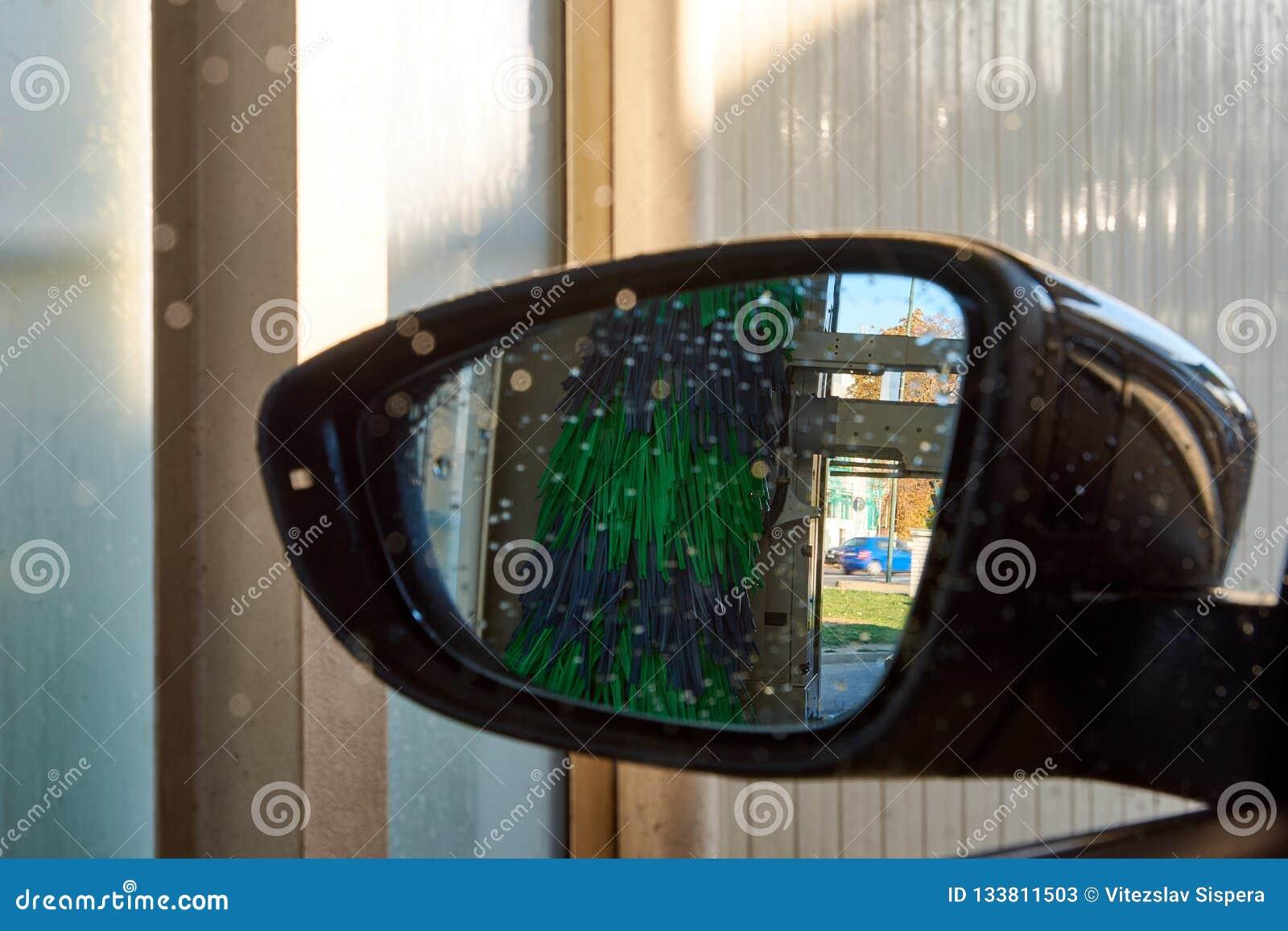Nahaufnahmefoto eines Rückspiegels innerhalb einer Waschanlage mit wate