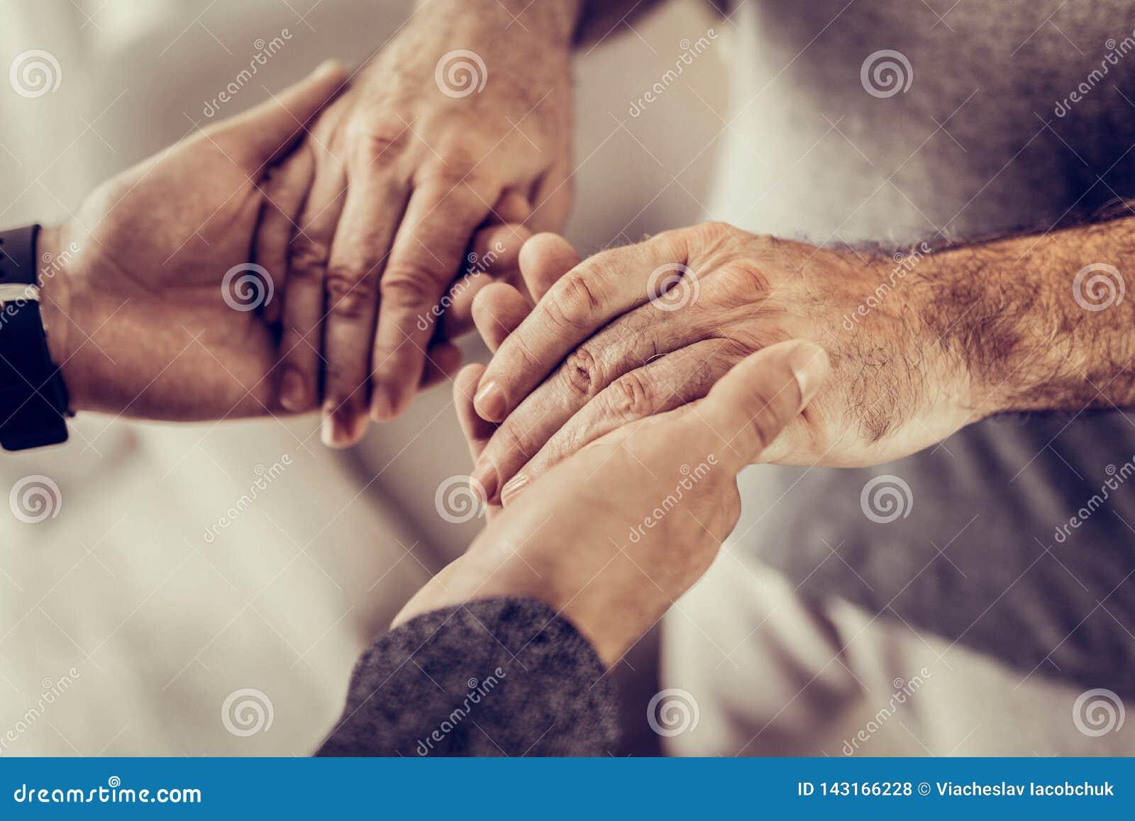 Nahaufnahmefoto von zwei männlichem Händchenhalten in den Händen