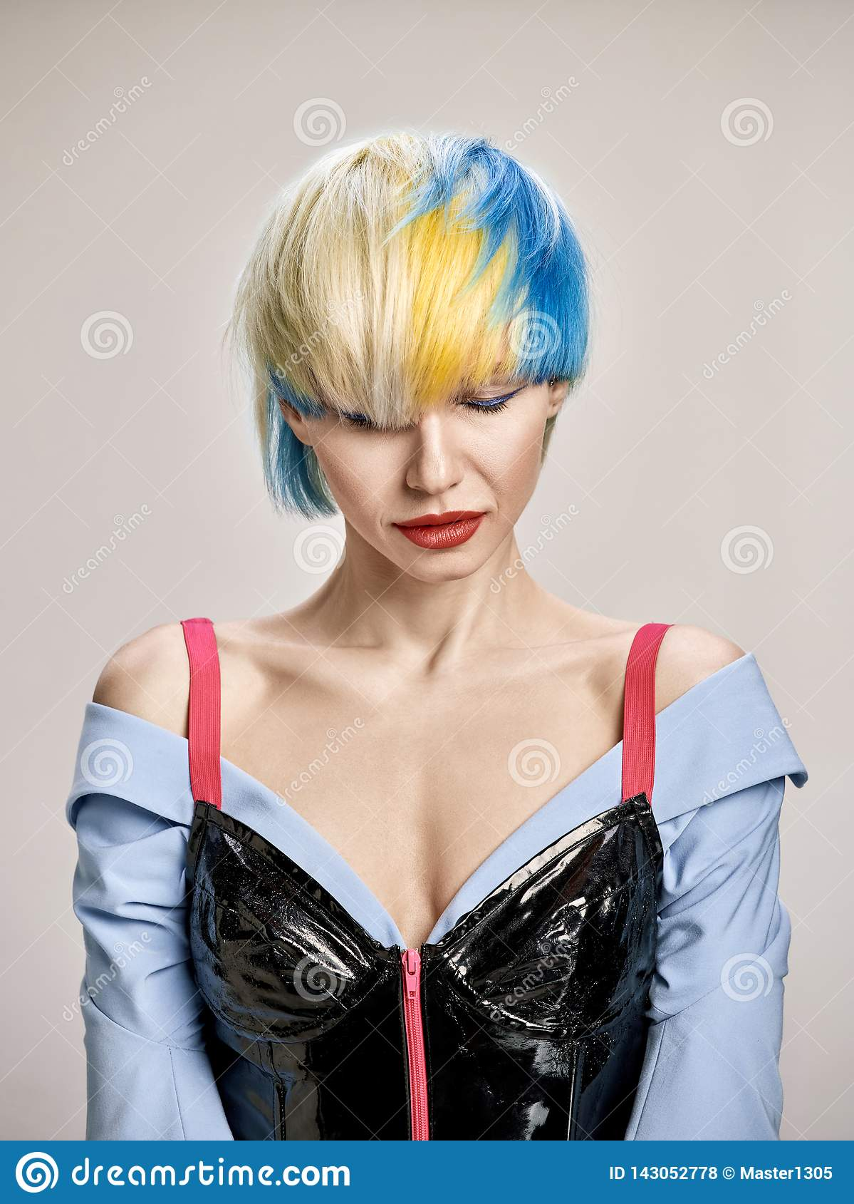 Nahaufnahmeinnenporträt des reizenden Mädchens mit dem blonden Haar Atelieraufnahme der würdevollen jungen Frau mit kurzem Haarsc