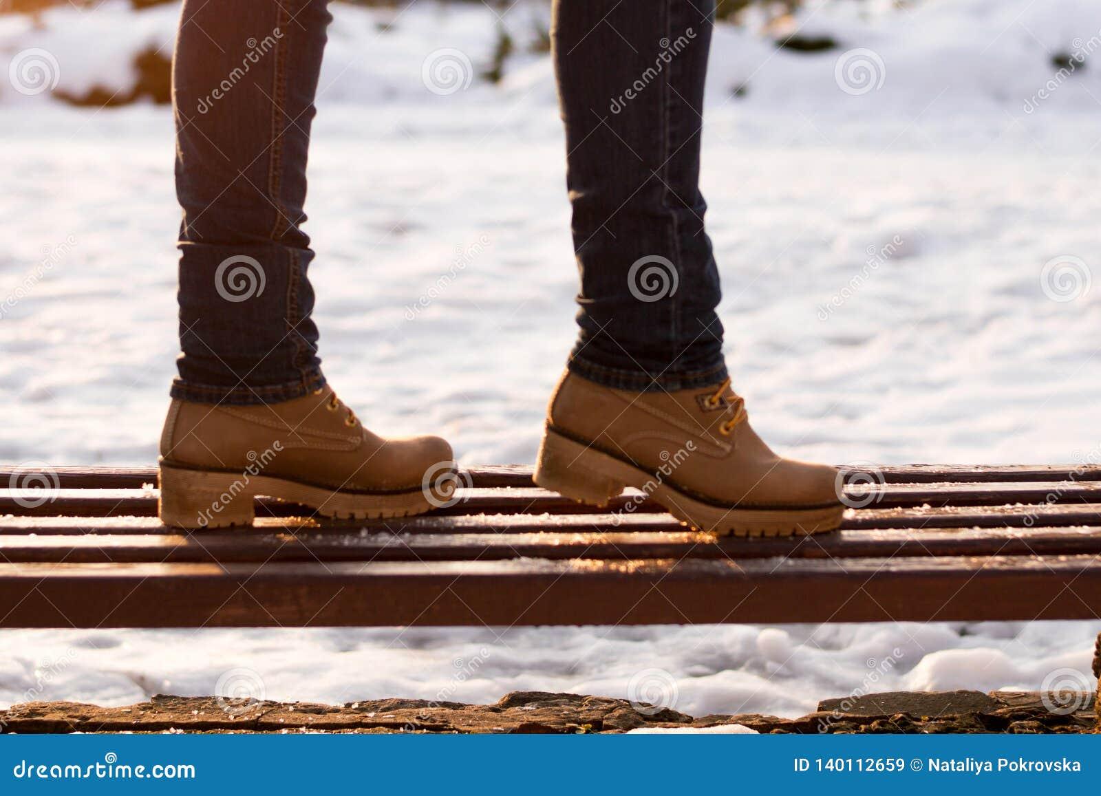 Nahaufnahmemädchenbeine auf Bank am sonnigen Tag des Winters auf unscharfem Hintergrund Romantisches Gehen in Park in der Oberbek