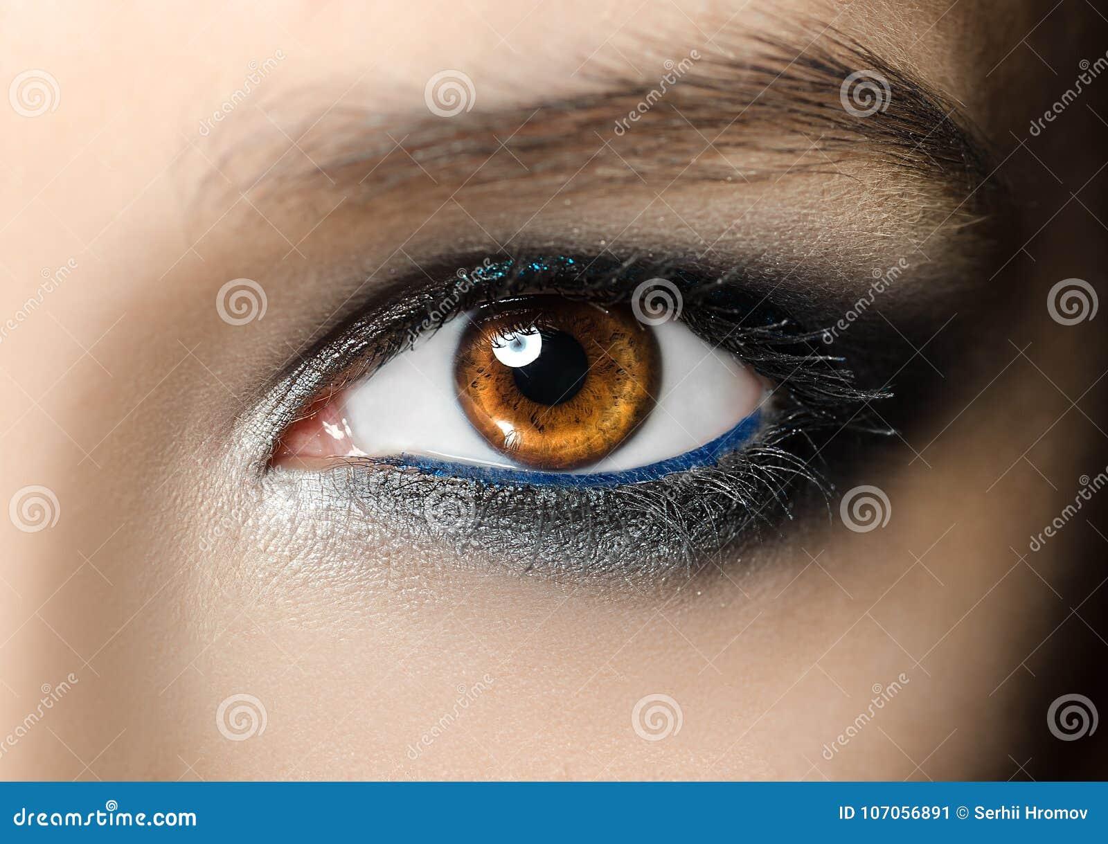 Nahaufnahmemakroporträt des weiblichen Gesichtes Menschliches Frauenauge mit Schönheitsmake-up und den langen natürlichen Wimpern