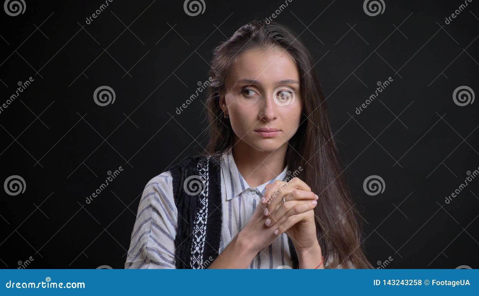 Nahaufnahmeporträt der jungen hübschen kaukasischen Frau, die durchdacht ist und zur Seite mit lokalisiertem Hintergrund schaut