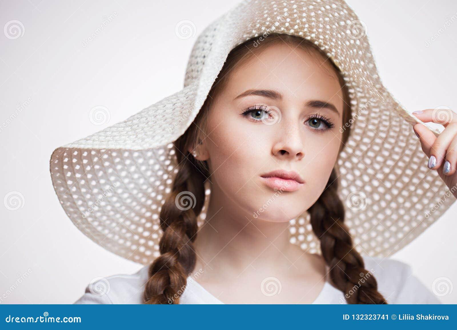 Nahaufnahmeporträt der jungen Schönheit einen Hut tragend und die Kamera auf weißem Hintergrund untersuchend Mädchen mit den lang
