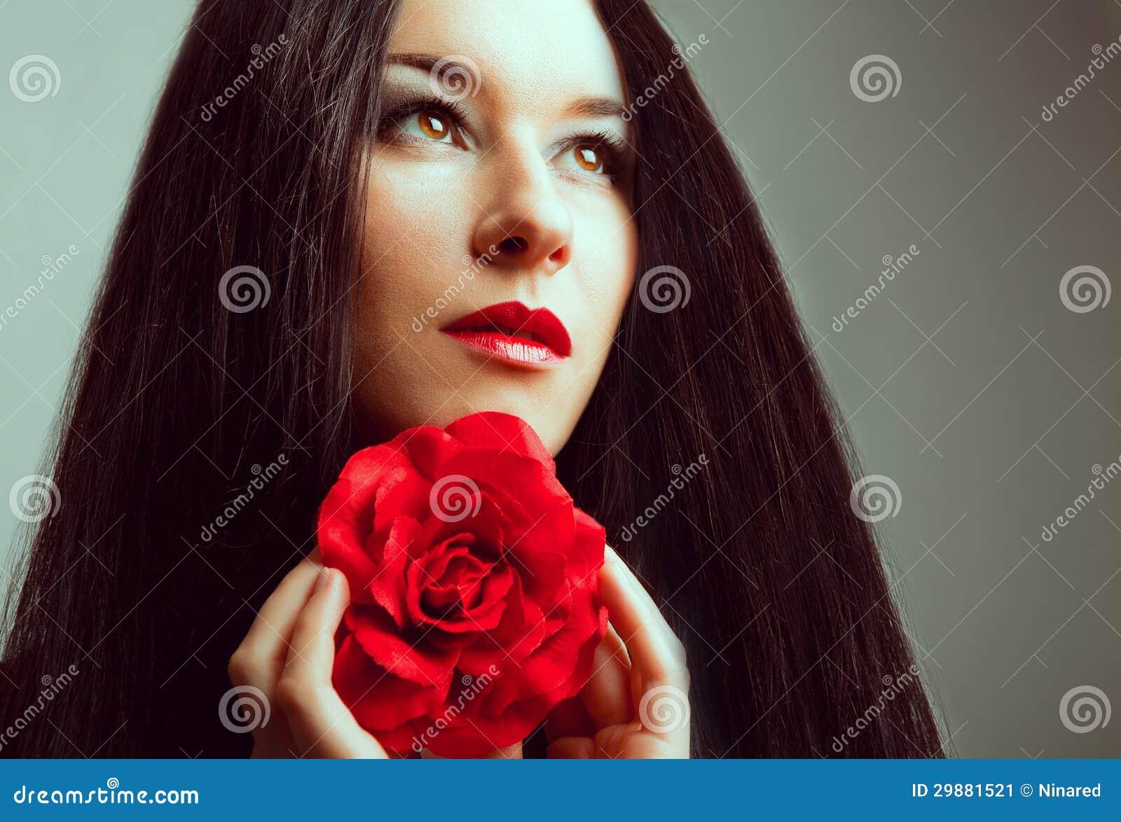 Nahaufnahmeporträt der schönen Brunettefrau mit Rotrose