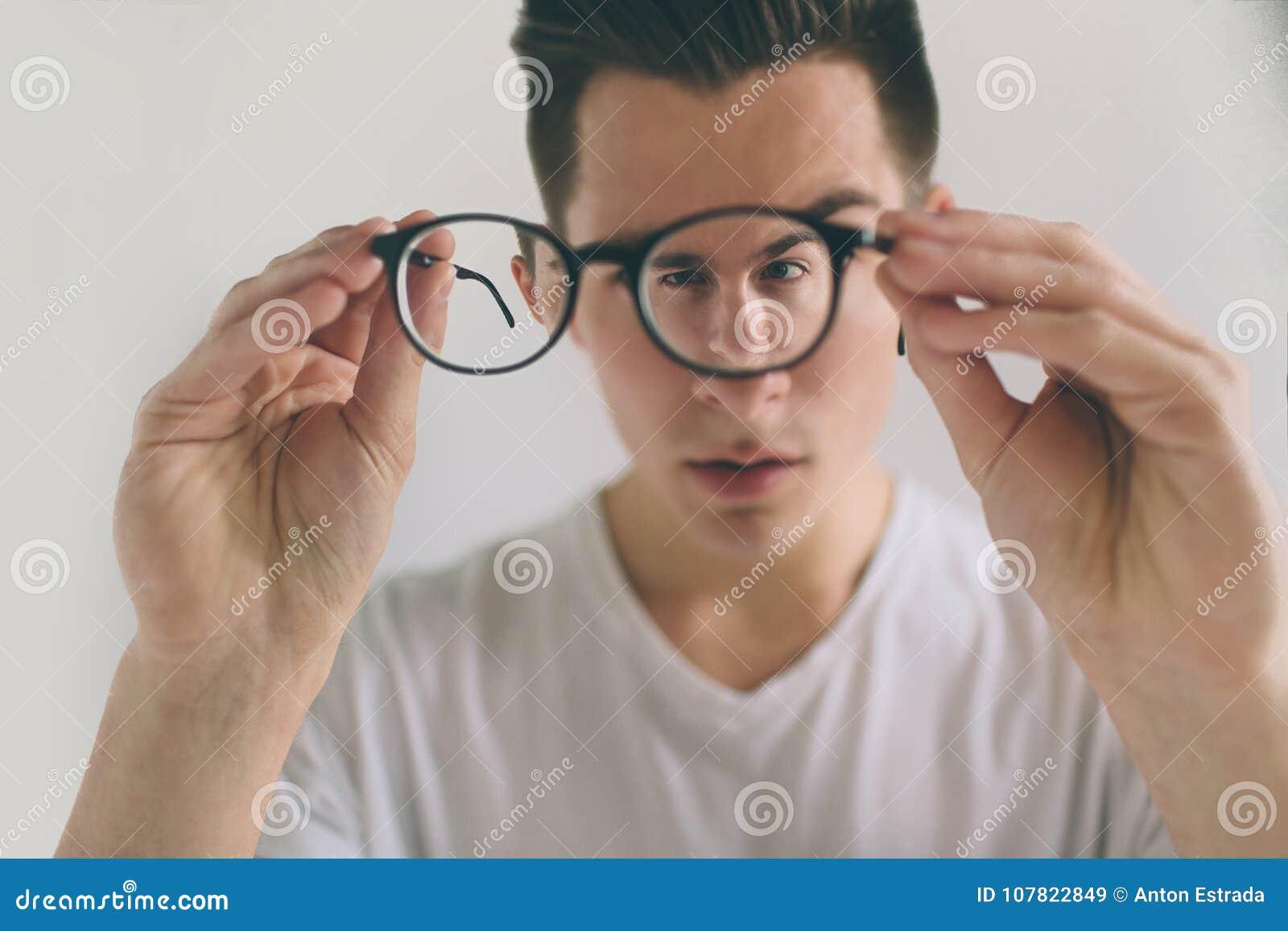 Nahaufnahmeporträt des jungen Mannes mit Gläsern Er hat Sehvermögenprobleme und schielt seine Augen ein wenig stattlich