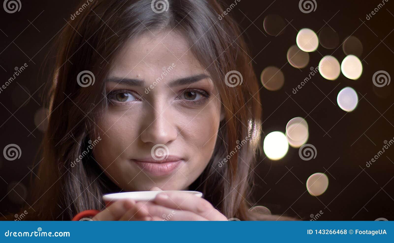 Nahaufnahmeporträt des kaukasischen brunette Mädchens mit Tasse Kaffee ruhig aufpassend in Kamera auf unscharfem Lichthintergrund