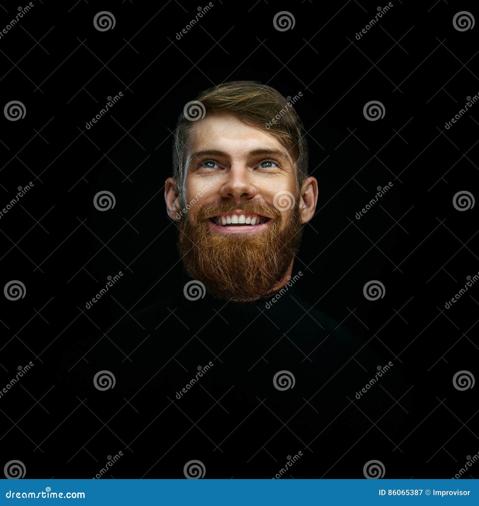 Nahaufnahmeporträt des Lachens des jungen bärtigen Mannes weared schwarzes tur