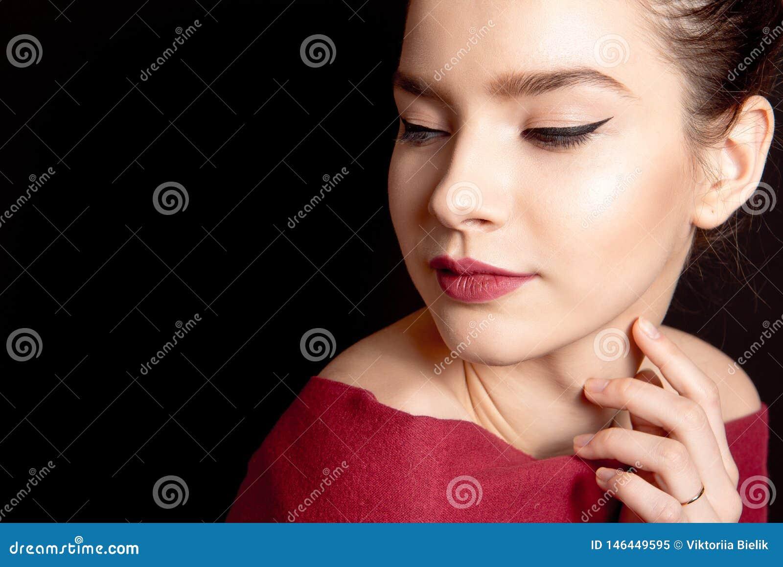 Nahaufnahmeporträt einer Frau mit klassischem Make-up mit einem schwarzen Pfeil und einer bloßen Lippe über ihren Schultern auf e