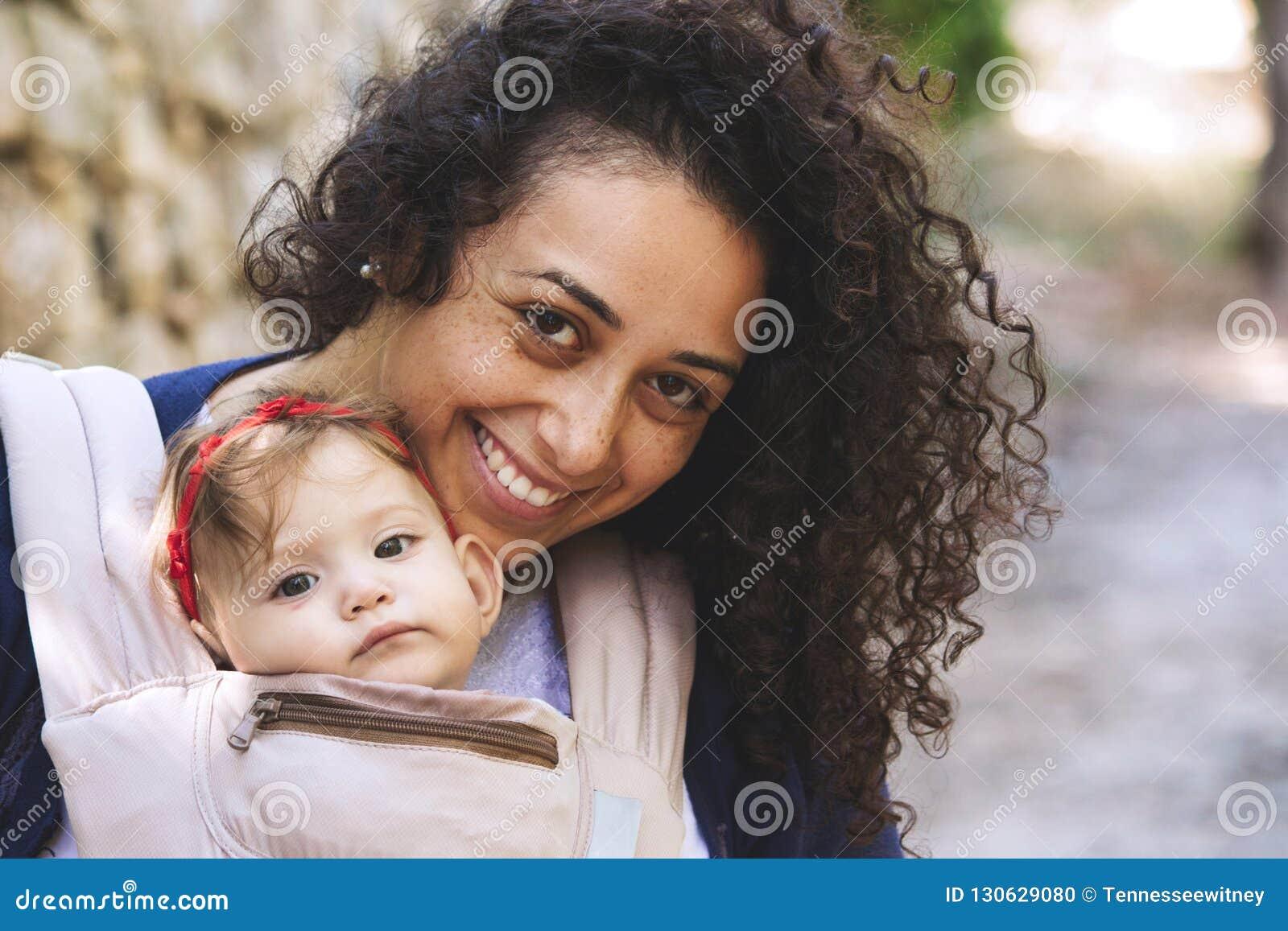 Nahaufnahmeporträt einer jungen attraktiven Mutter, die ein Baby in einer Riemenfördermaschine trägt