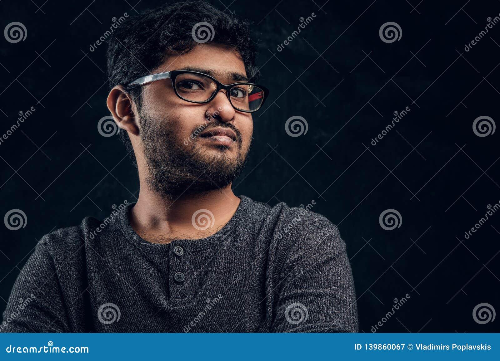 Nahaufnahmeporträt eines jungen indischen Kerls im Eyewear und in zufälliger Kleidung, die eine Kamera im Studio betrachten