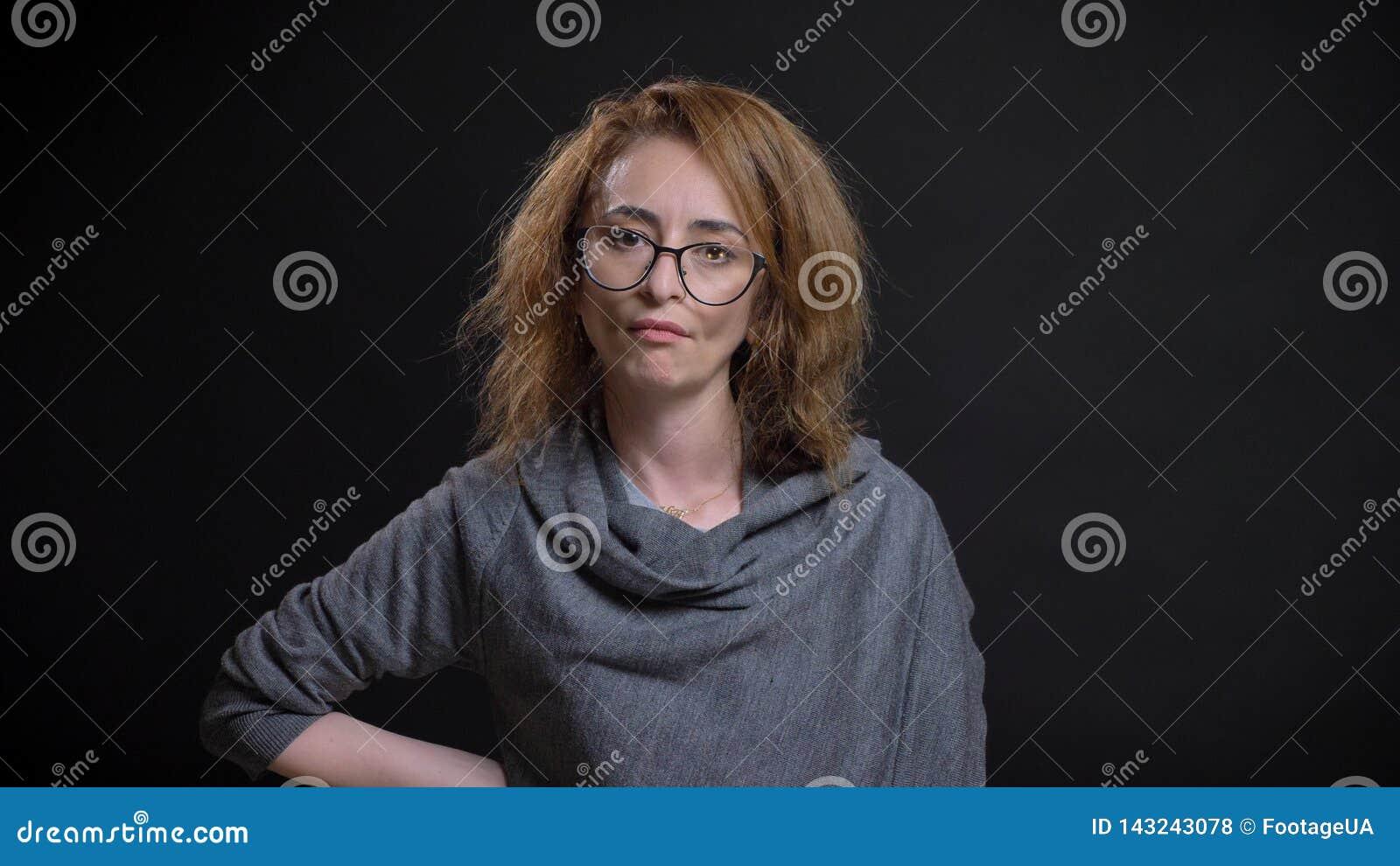 Nahaufnahmeporträt extravaganten Rothaarigen der von mittlerem Alter weiblich in den Gläsern, die verärgert und wütend sind und H