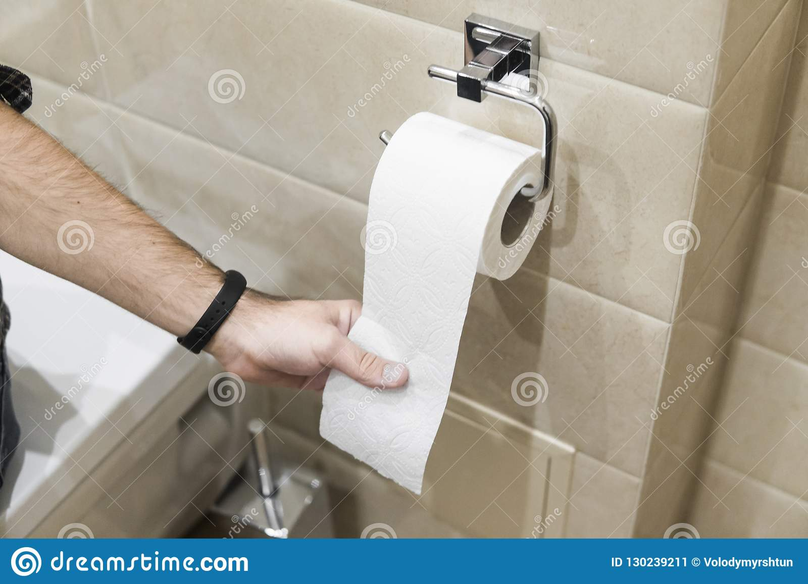Nahaufnahmerollentoilettenpapier in der Toilette mit Handdem ziehen