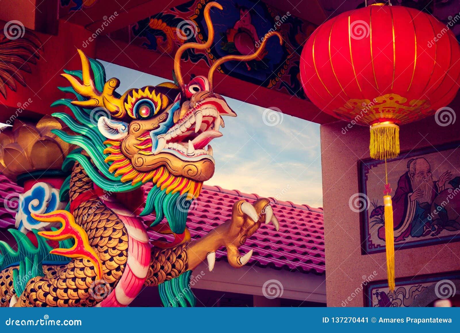 Nahaufnahmestatue eines Drachen eingewickelt um einen Pfosten mit chinesischer Laterne im chinesischen Tempel
