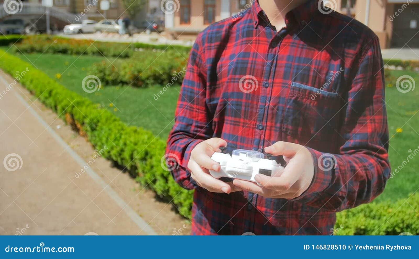 Nahaufnahmezeitlupevideo des kleinen Spielzeugdrohne, das Junge entfernt, bemannt Hand im Park Jugendlicher, der mit kleinem Brum stock video footage
