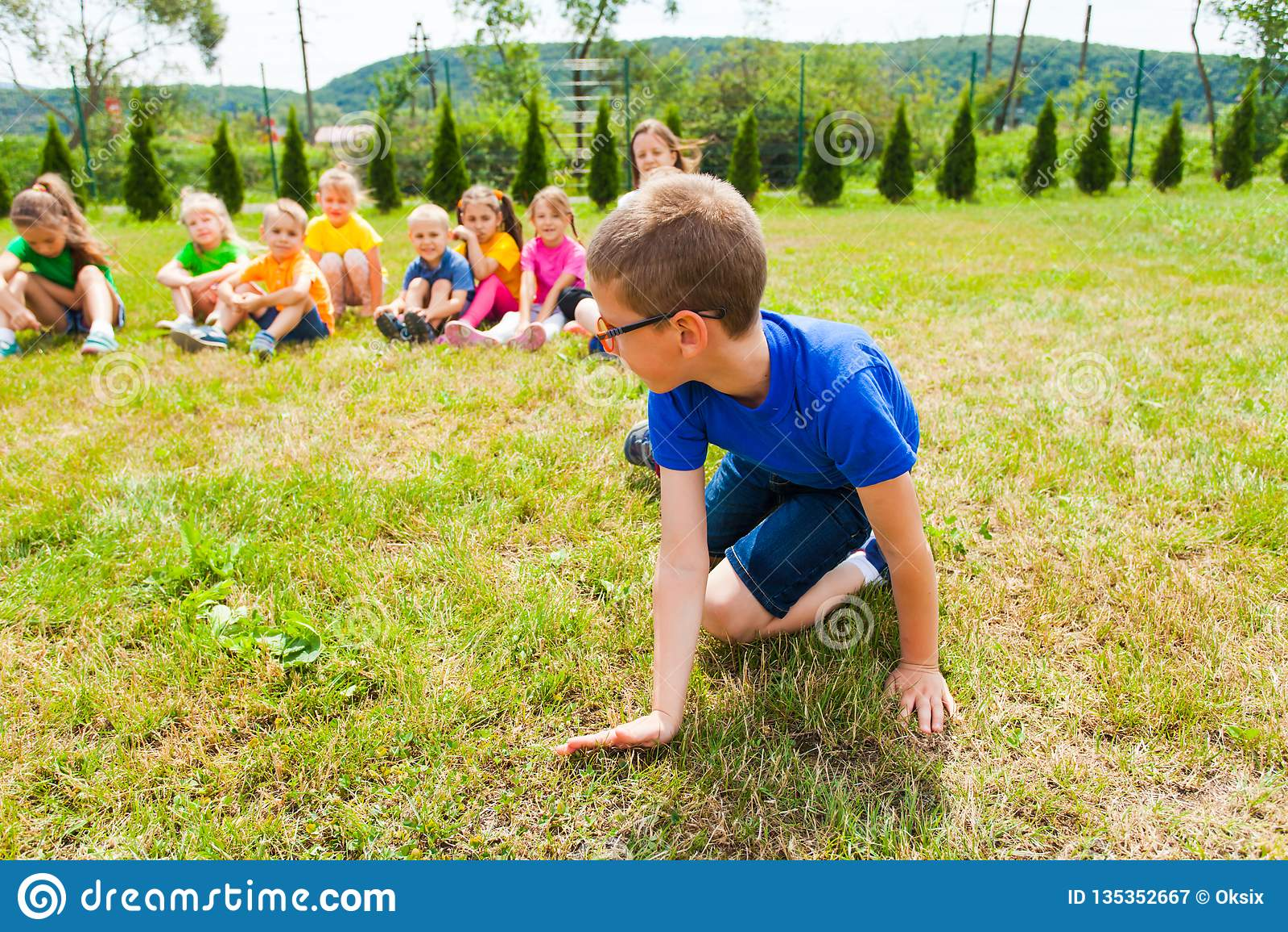 Nahe Ansicht des Jungen stehend auf seinen Knien, Gruppe Kinder hinter ihm