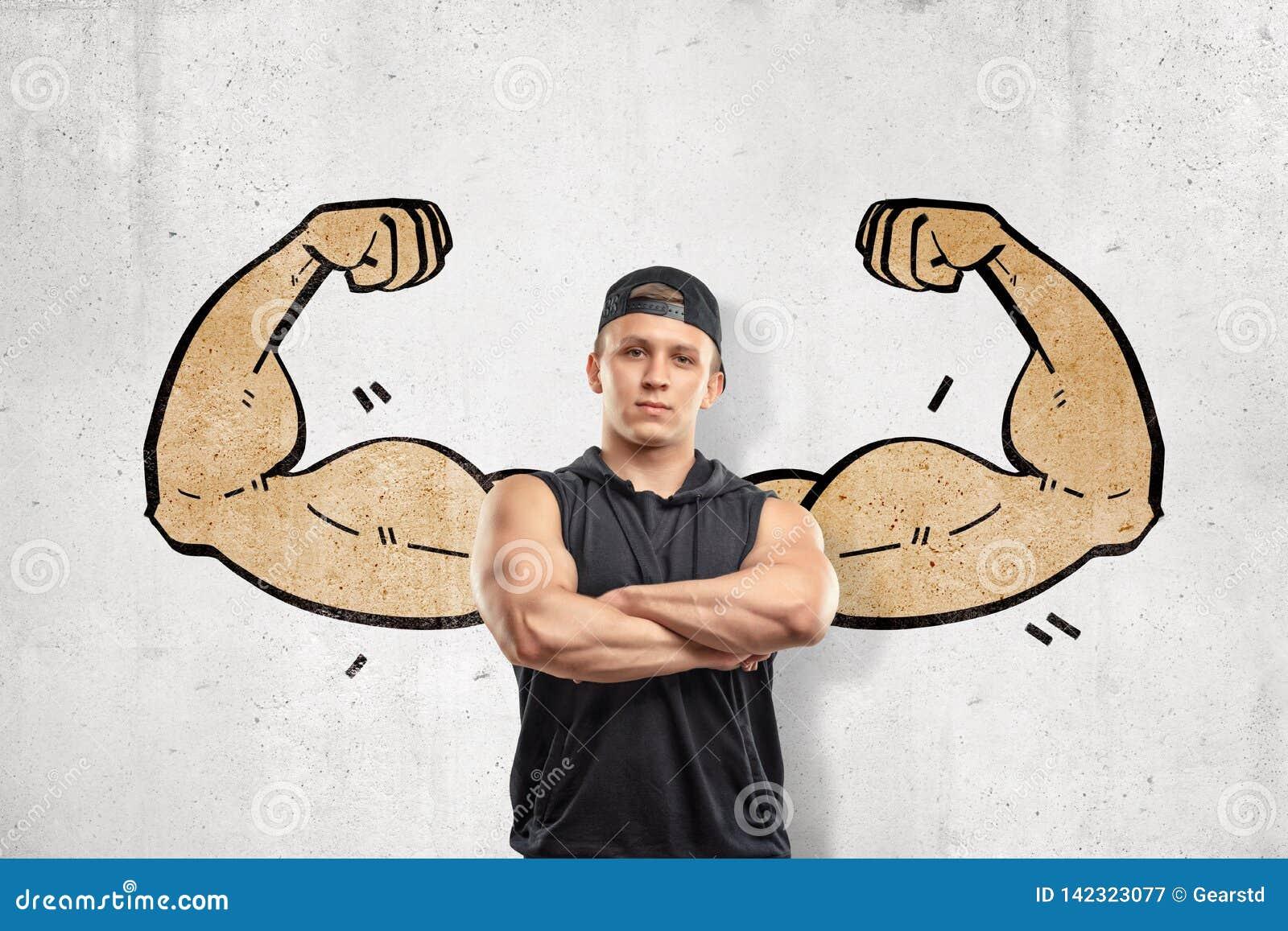 Nahe ehrliche Ansicht des jungen athletischen Mannes mit den Armen kreuzte und stand gegen Wand mit Zeichnung von großen muskulös