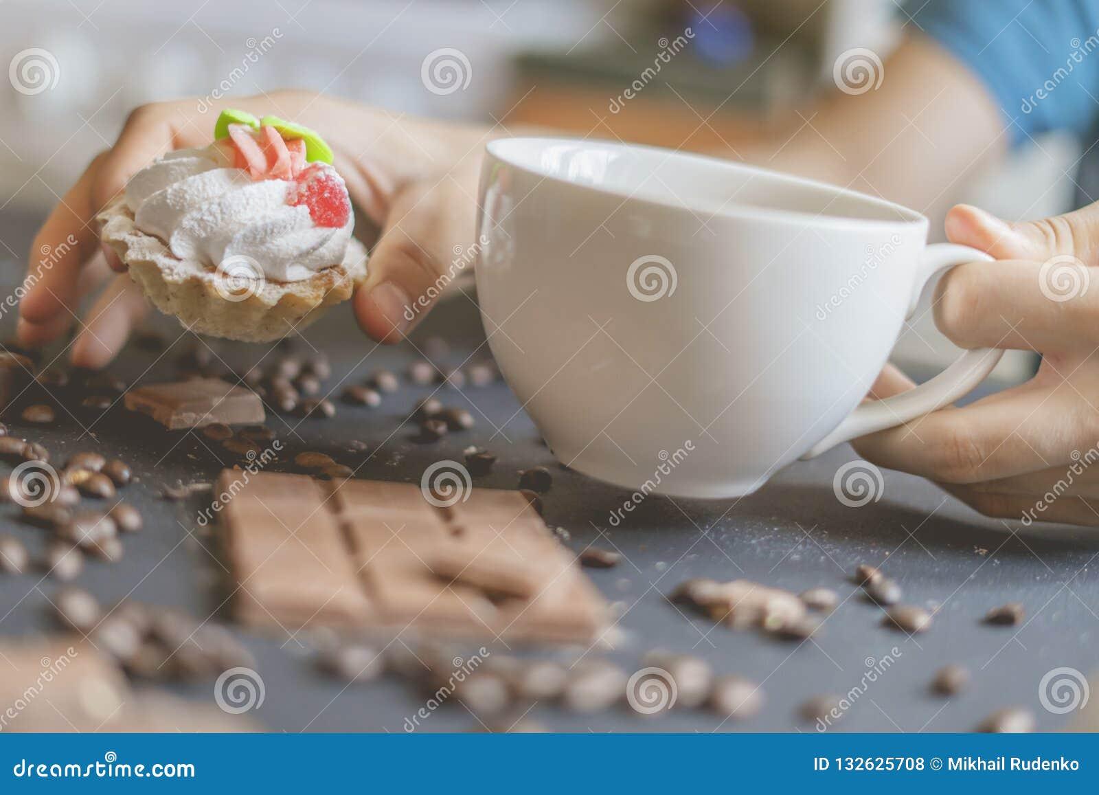 Nahe hohe Hand, die morgens einen süßen Kuchen und einen Tasse Kaffee auf der dunklen Tabelle f hält
