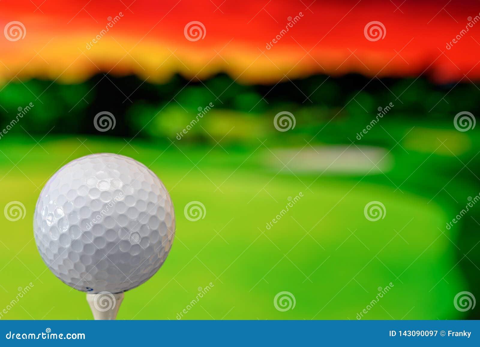 Nahes hohes Foto eines Golfballs im Golfplatz in einem warmen Sonnenunterganglicht