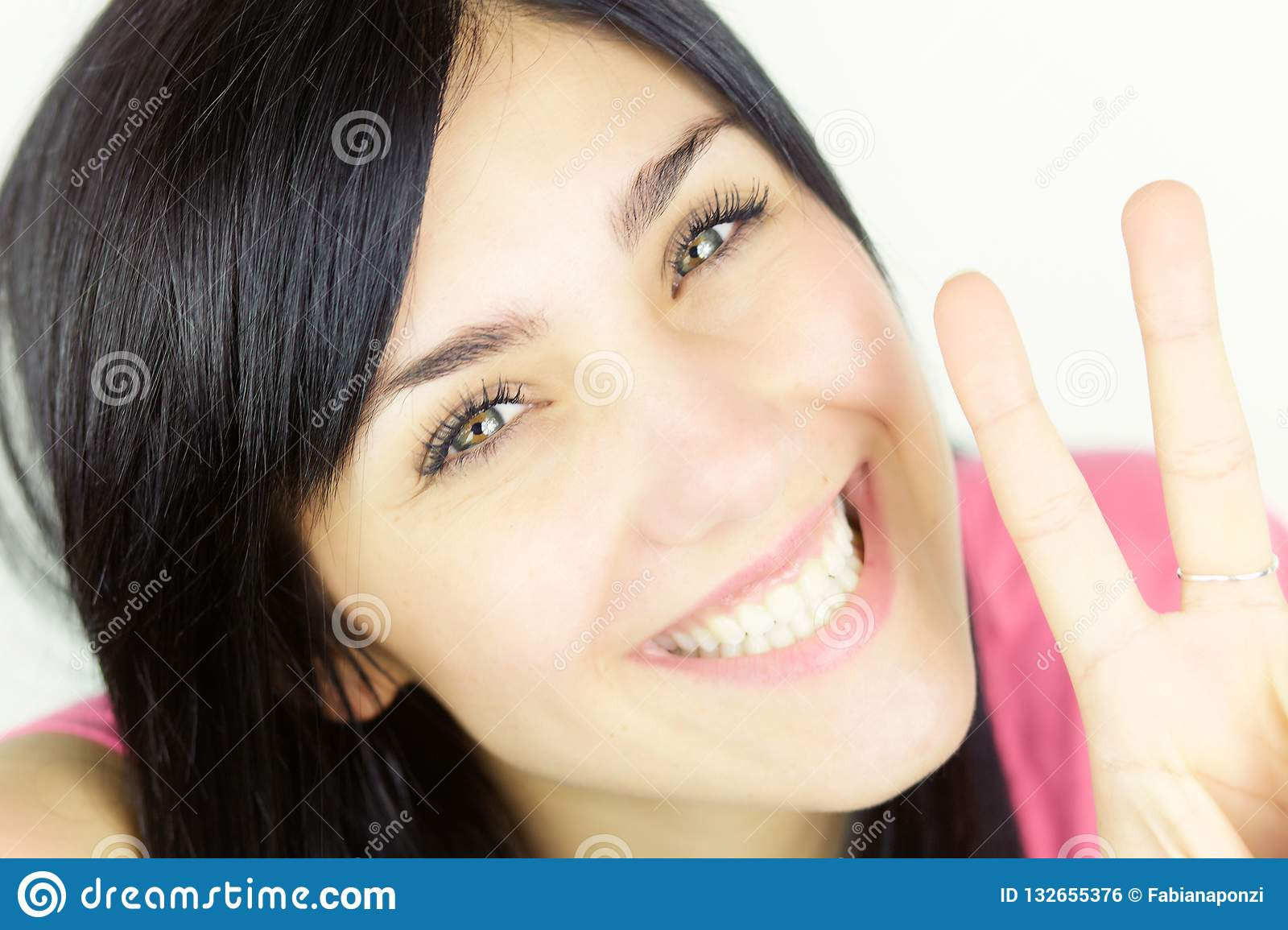 Nahes hohes Porträt der netten Frau mit dem Lächeln der grünen Augen