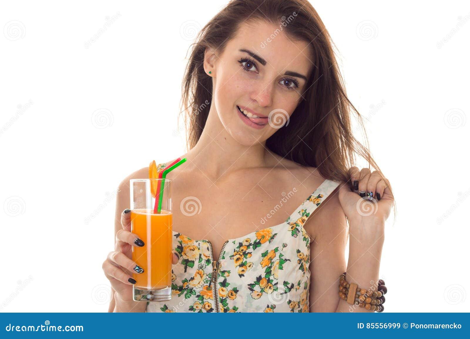 Nahes hohes Porträt der Sommerzeit des jungen reizend Mädchens in der hellen Kleidung mit dem Cocktail bei der Handaufstellung lo