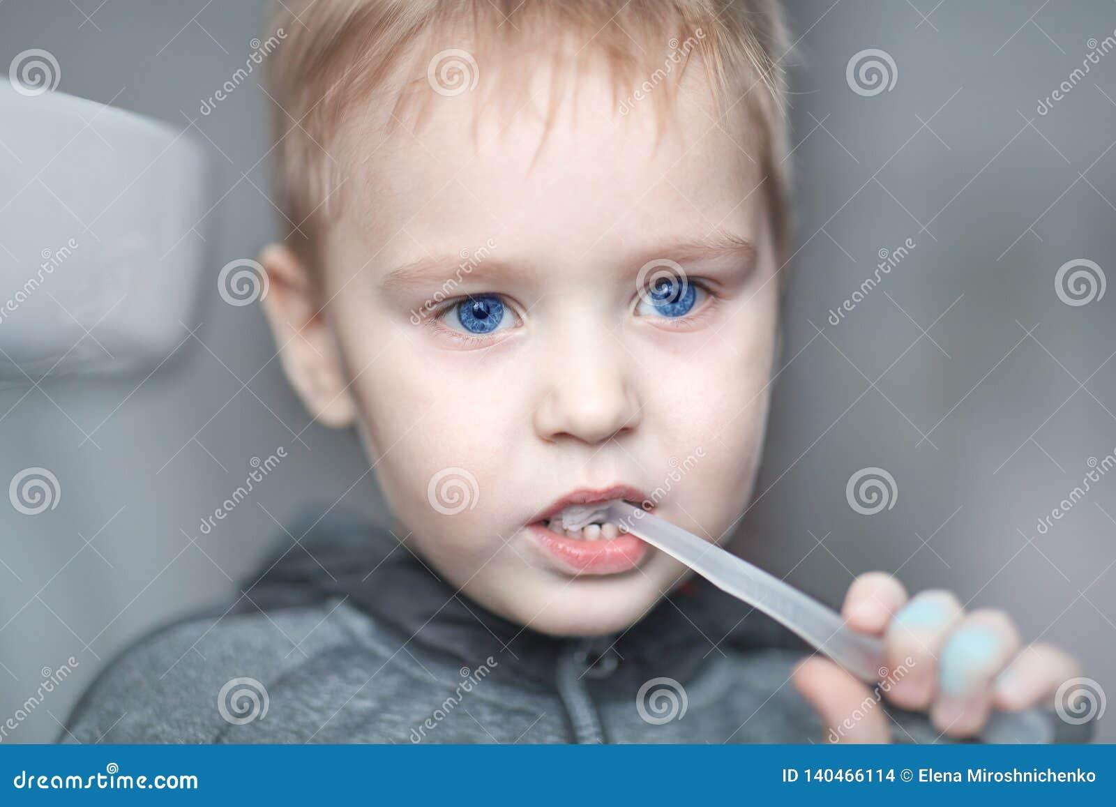 Nahes hohes Porträt des netten kaukasischen Babys mit dem sehr ernsten Gesichtsausdruck, der die Zähne mit Zahnbürste, allein säu