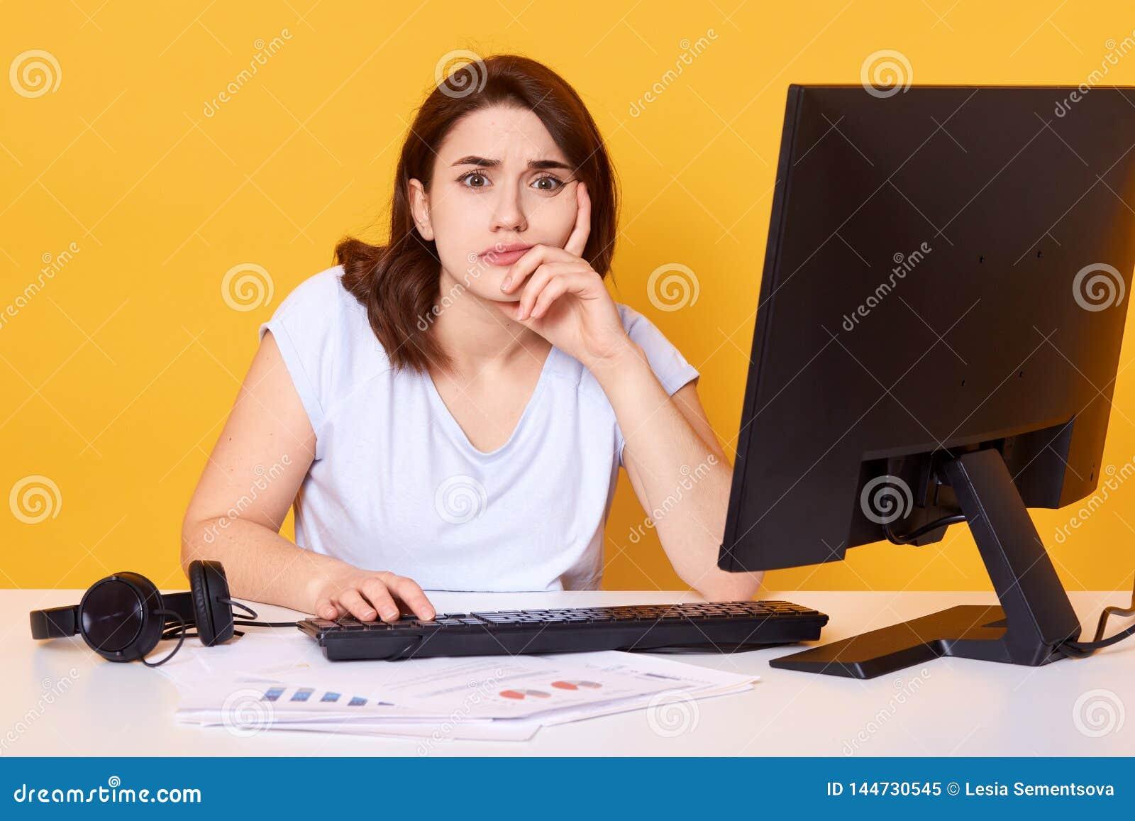Nahes hohes Porträt des recht jungen weiblichen Studenten unter Verwendung des Tischrechners in einer Collegebibliothek für das
