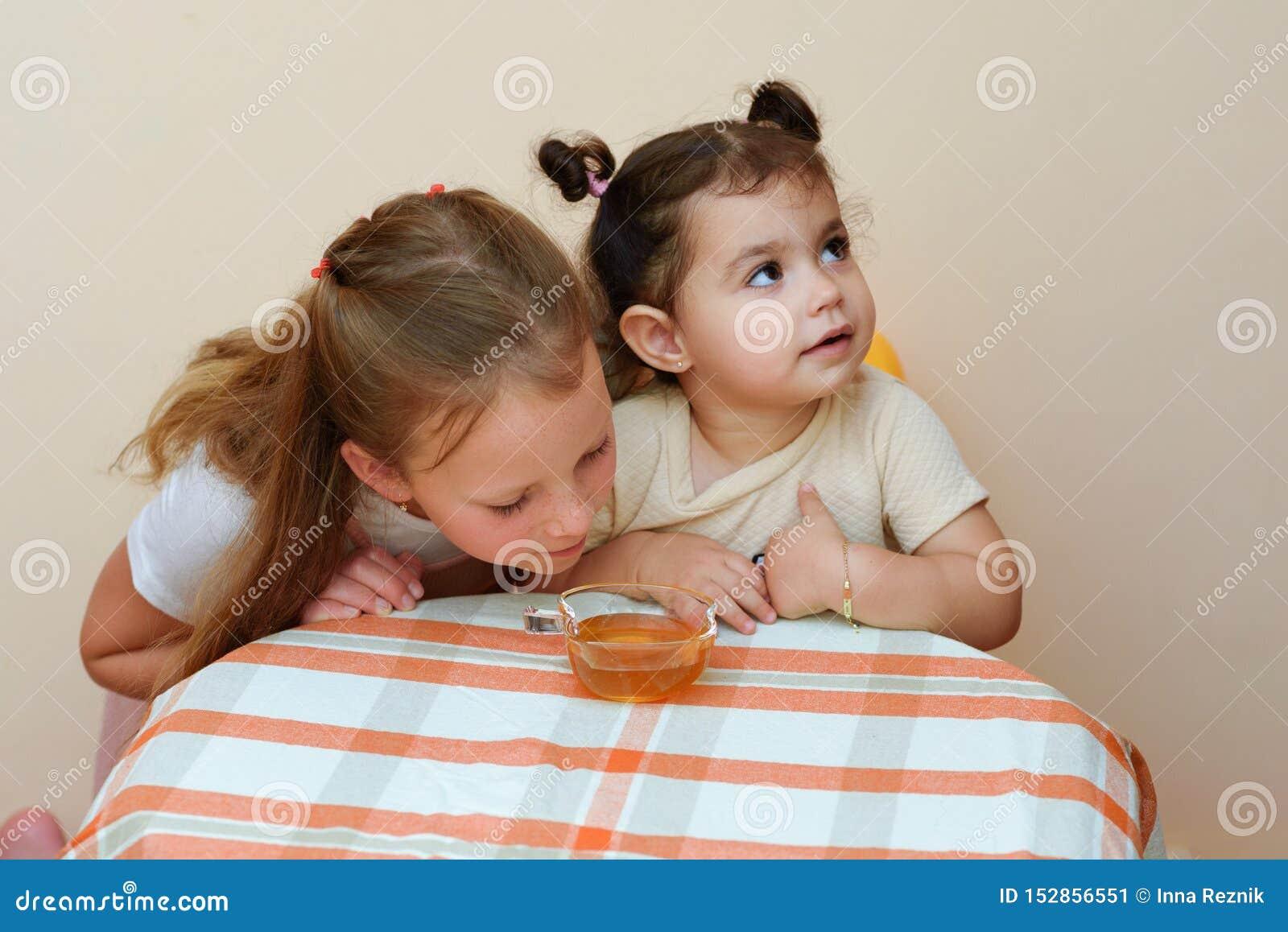 Nahes hohes Porträt lustigen netten kleinen Mädchens zwei Honig im Haus essen