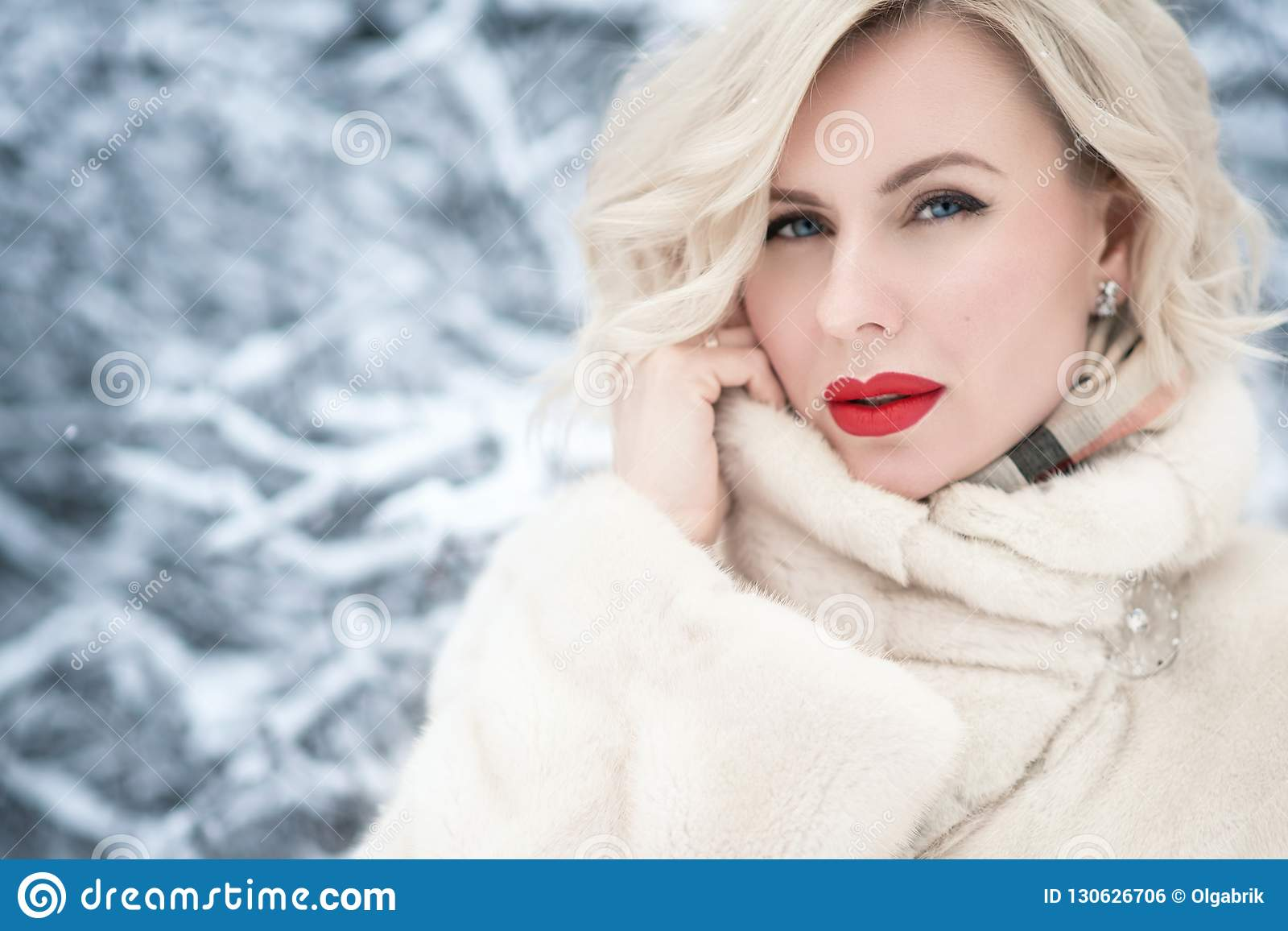 Nahes hohes Porträt schöner blonder blauäugiger Dame mit perfektem bilden das Halten eines Kragens ihres luxuriösen Pelzmantels