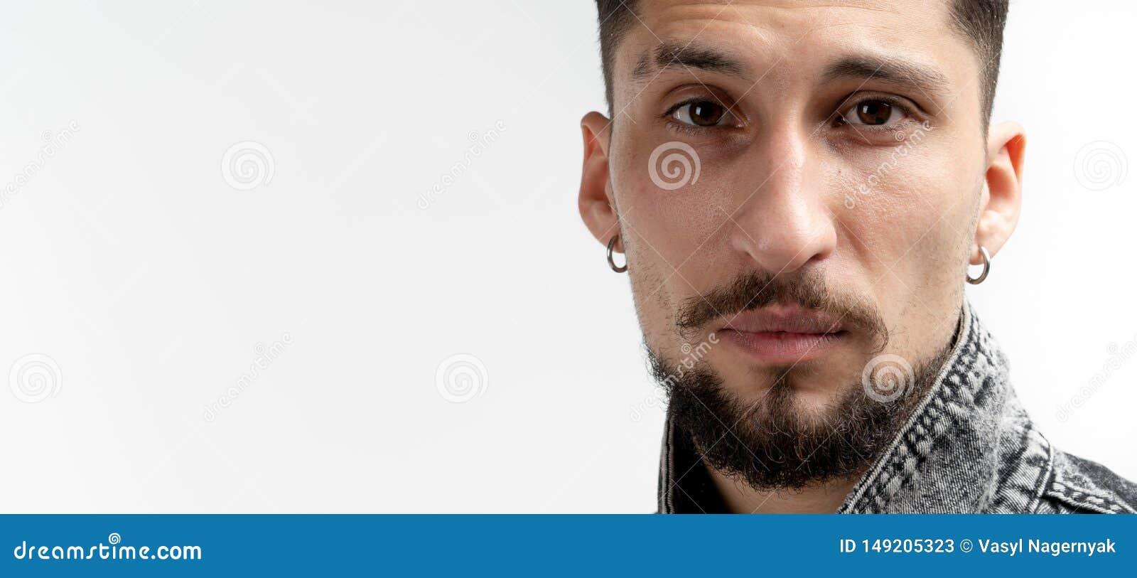 Nahes hohes Portr?t des jungen ernsten b?rtigen Mannes im Denimhemd, dass, die Kamera betrachtend lokalisiert ?ber wei?em Hinterg