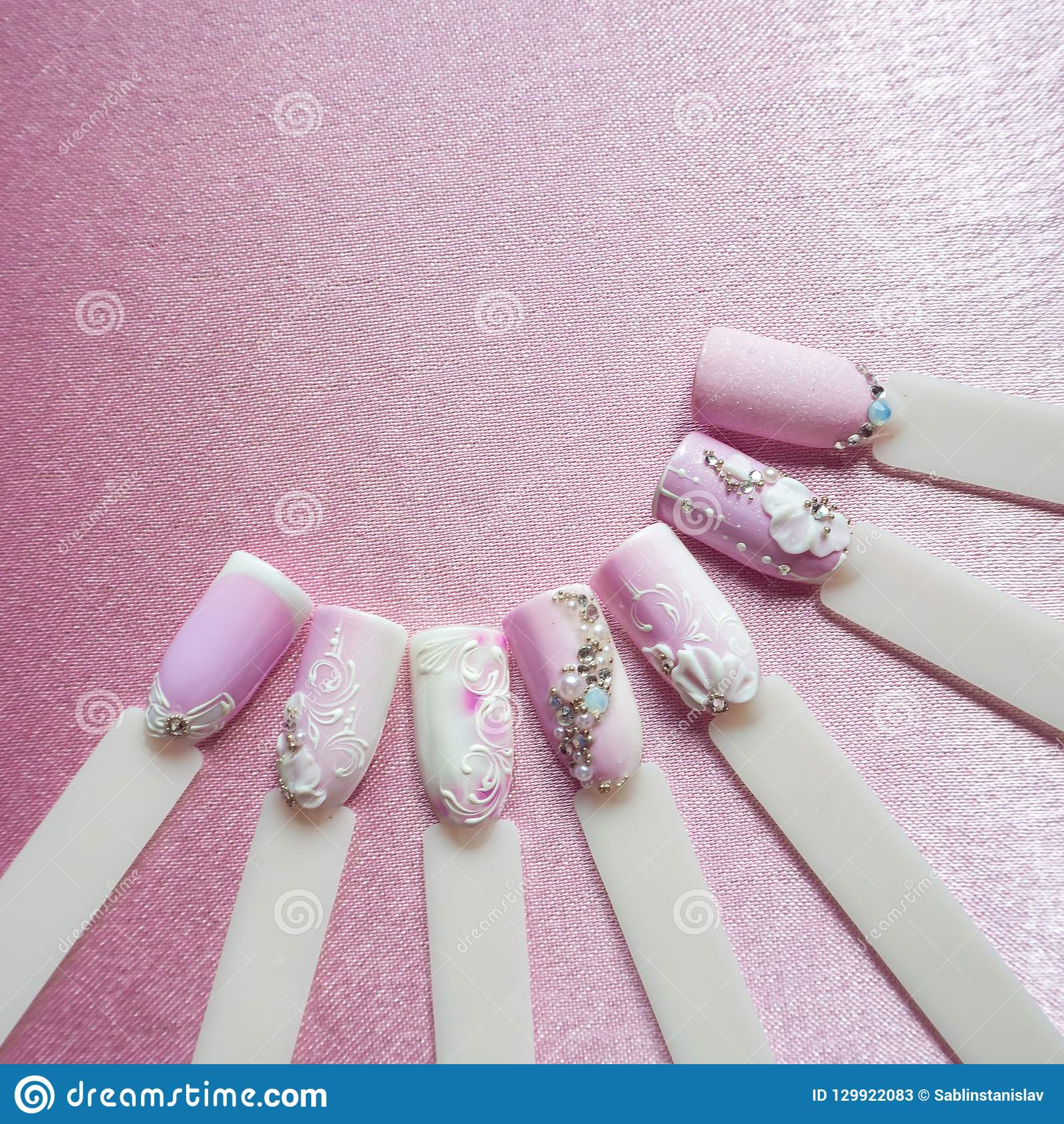 Nail art design with rhinestones on pink background.