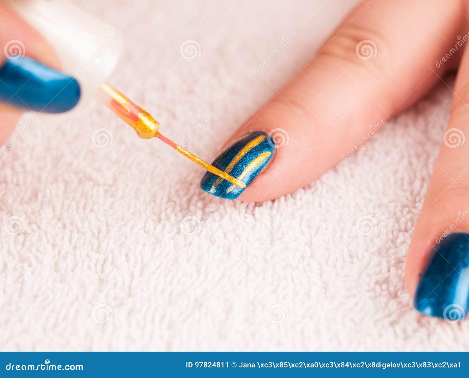 Nail art - painting gold stripes on dark blue base polish
