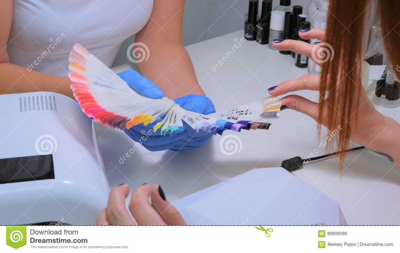 Nail technician shows the color palette of nail services in beauty salon