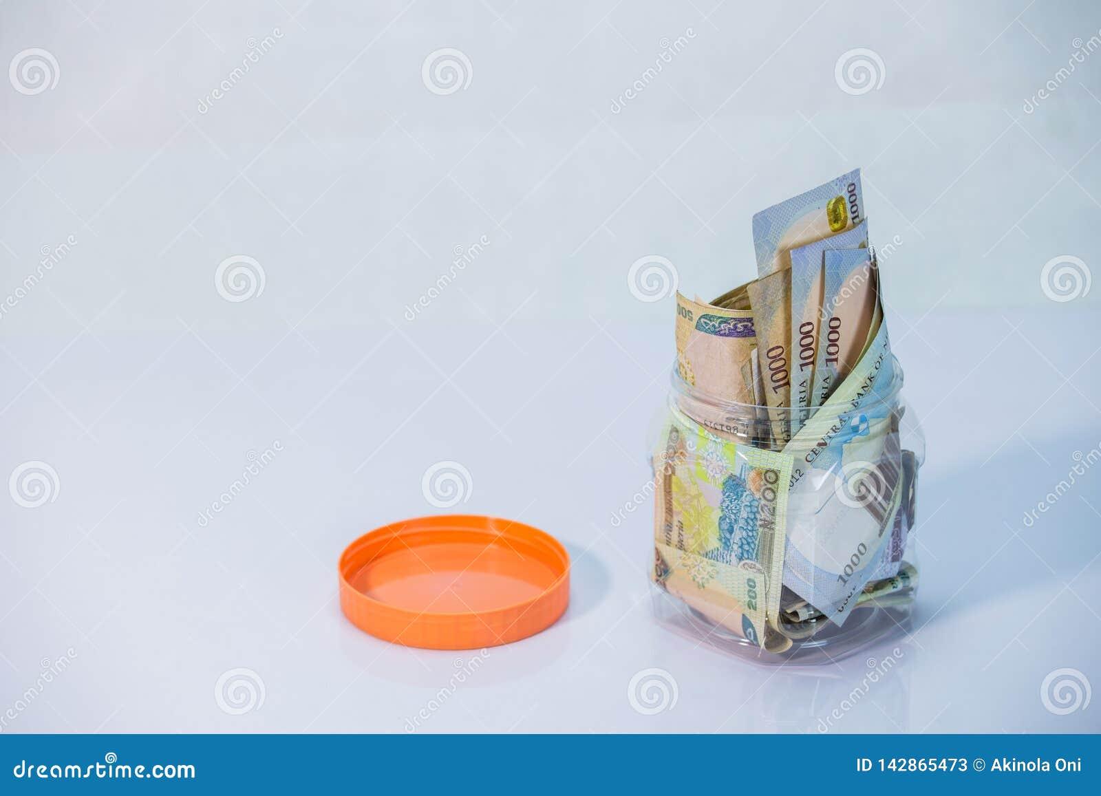 Nairaanmärkningar i en exponeringsglaskrus - begrepp av besparingen