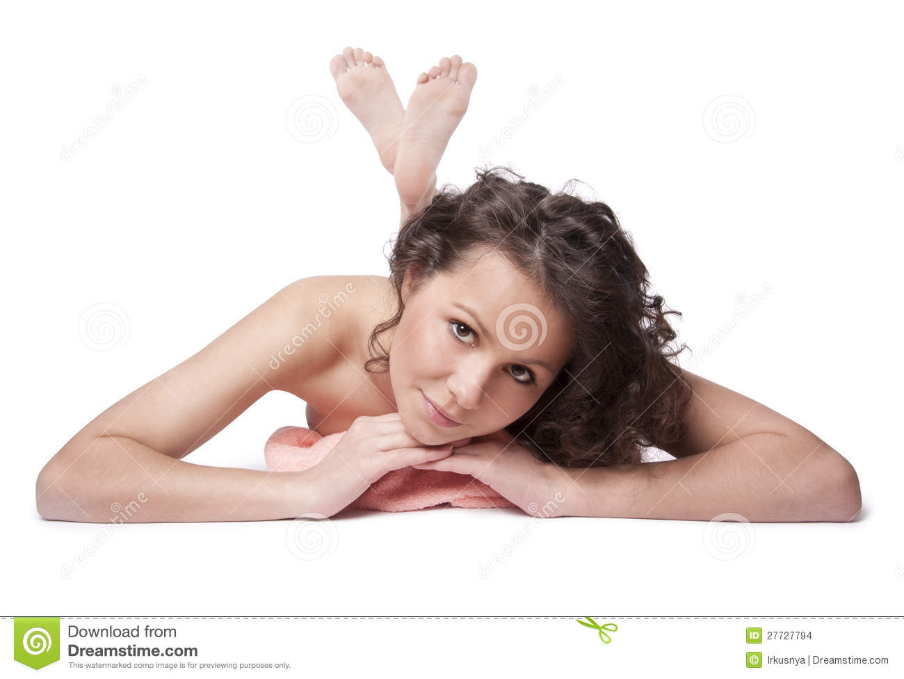 Naked beautiful woman smiling and lying on a towel