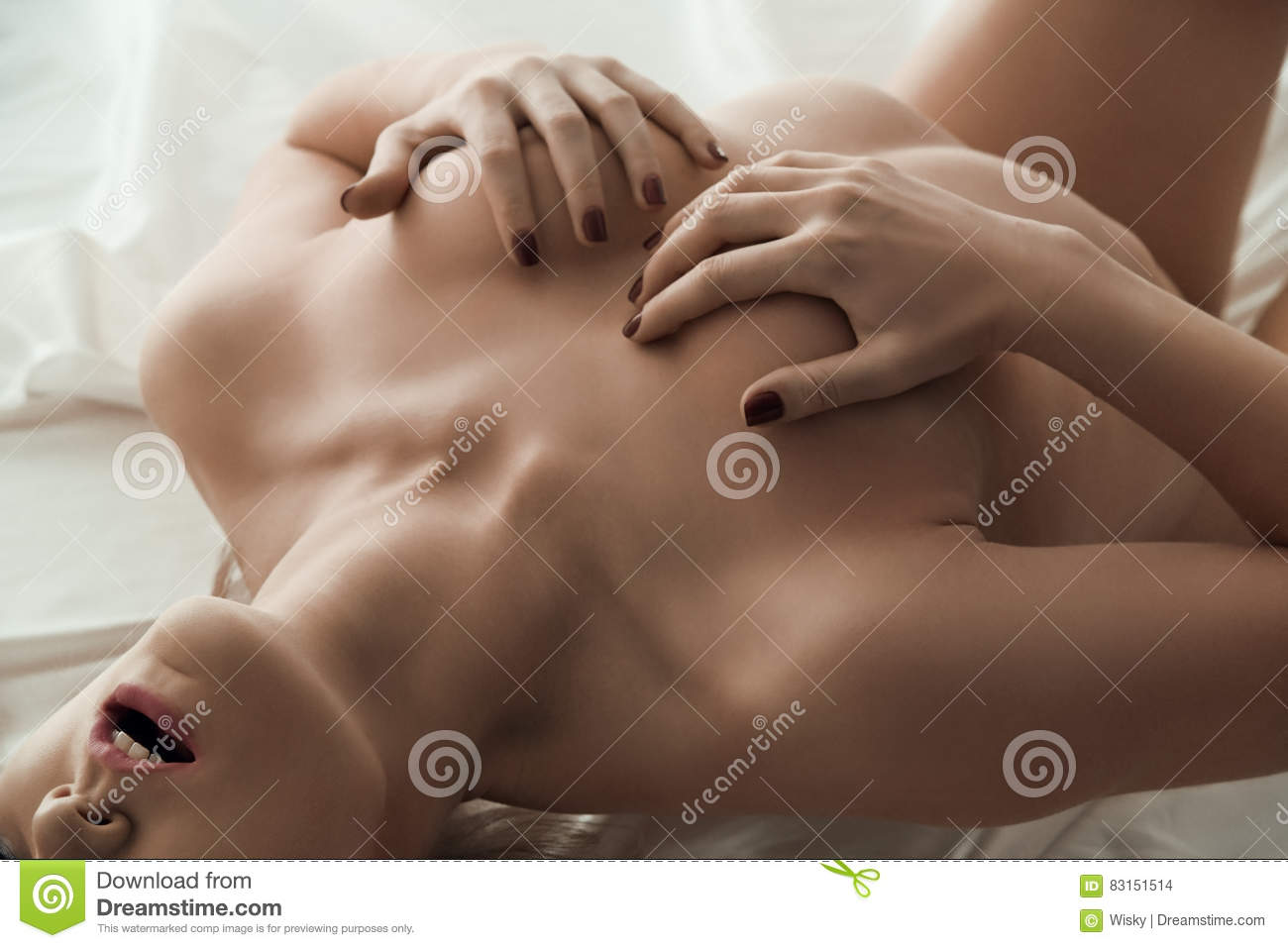 Naked Girl Holding Hands On Breasts Lying In Bed Stock Photo